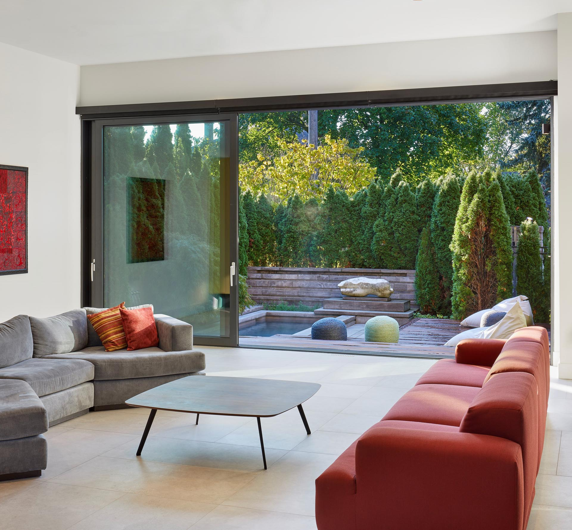 Large sliding glass doors connect the interior to the outdoor space and pool at the front of the home.