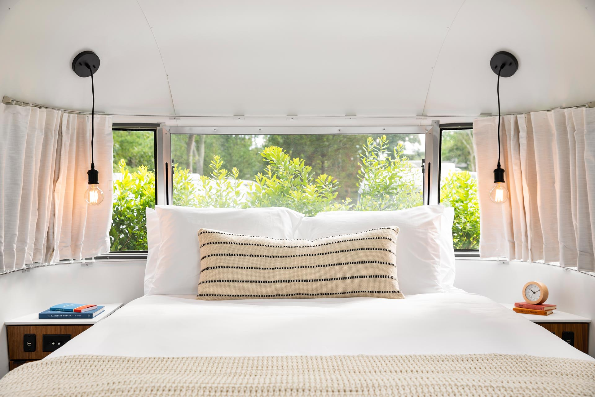 A remodeled Airstream bedroom is furnished with a queen bed, built-in side tables, and a pair of simple pendant lights.