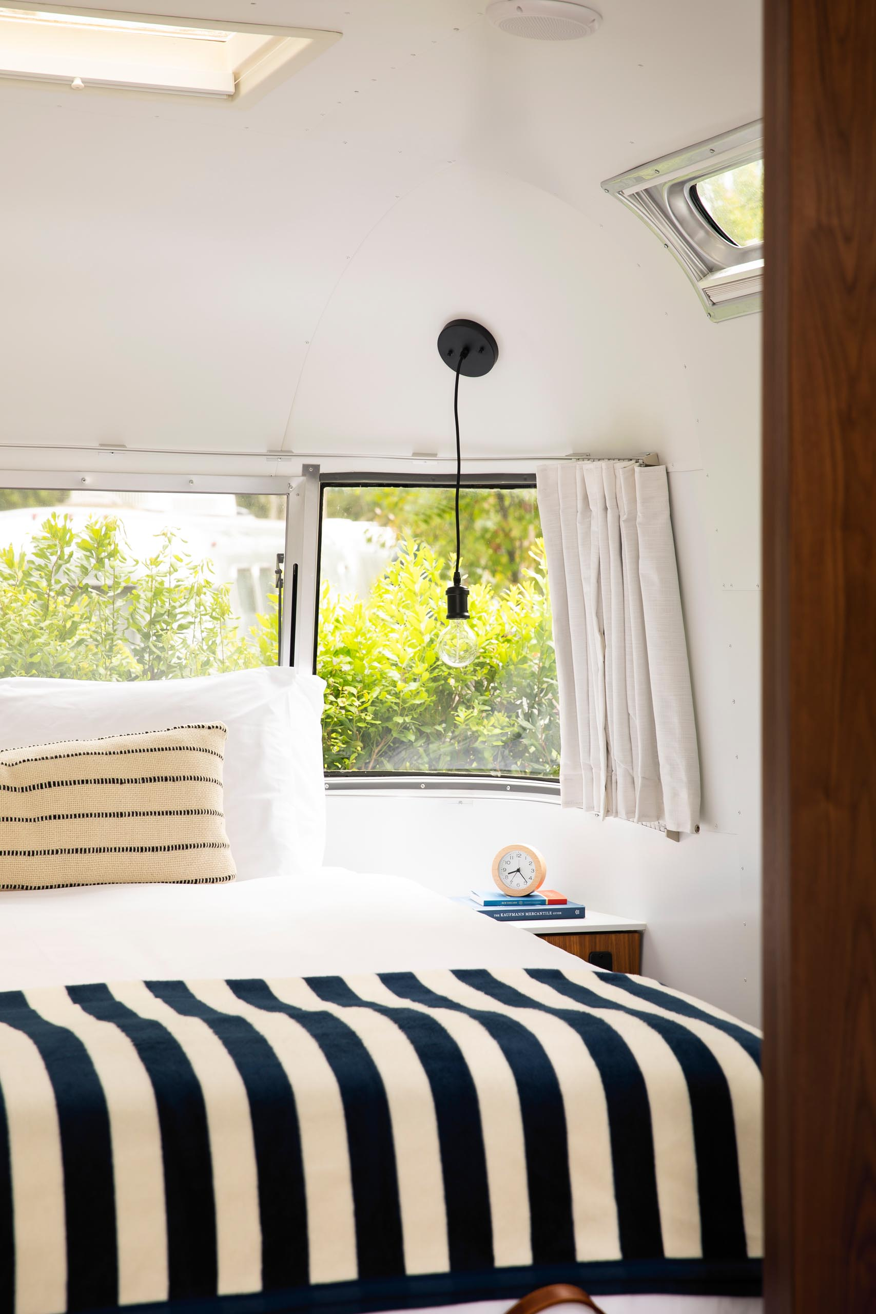 A remodeled Airstream bedroom is furnished with a queen bed, built-in side tables, and a pair of simple pendant lights. A panoramic window fills the small space with natural light and views of the gardens, while at night the curtains can be closed for a more cozy and private atmosphere.