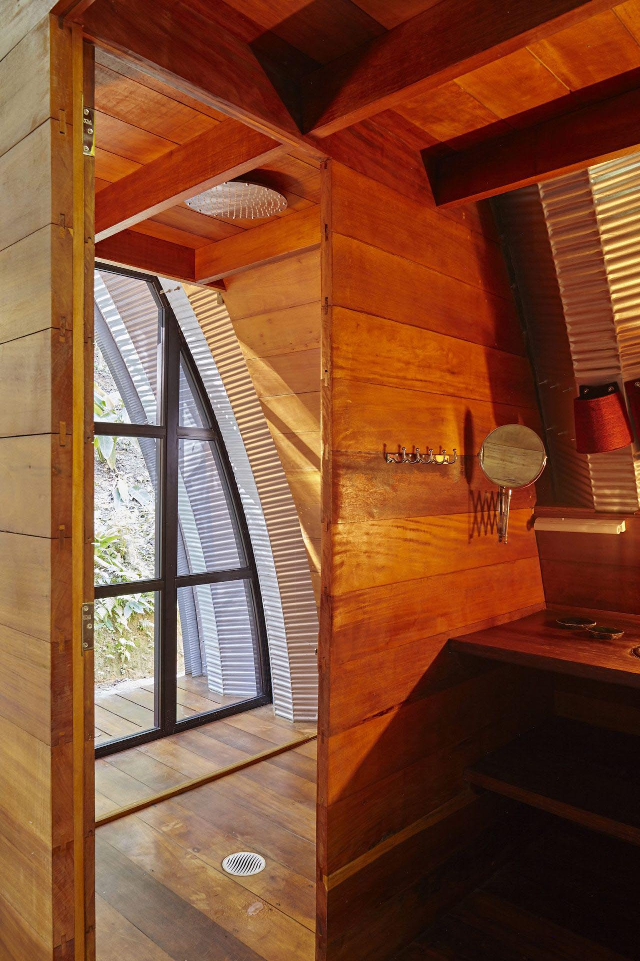 A modern bathroom lined with wood, that has a shower with tree views.
