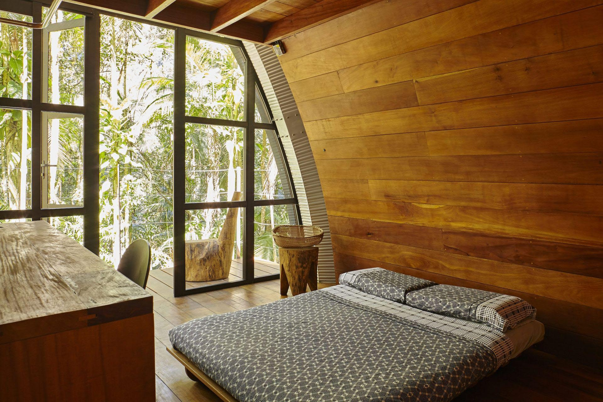 Wood details adds a warmth to the bedroom, while a door opens to the deck.