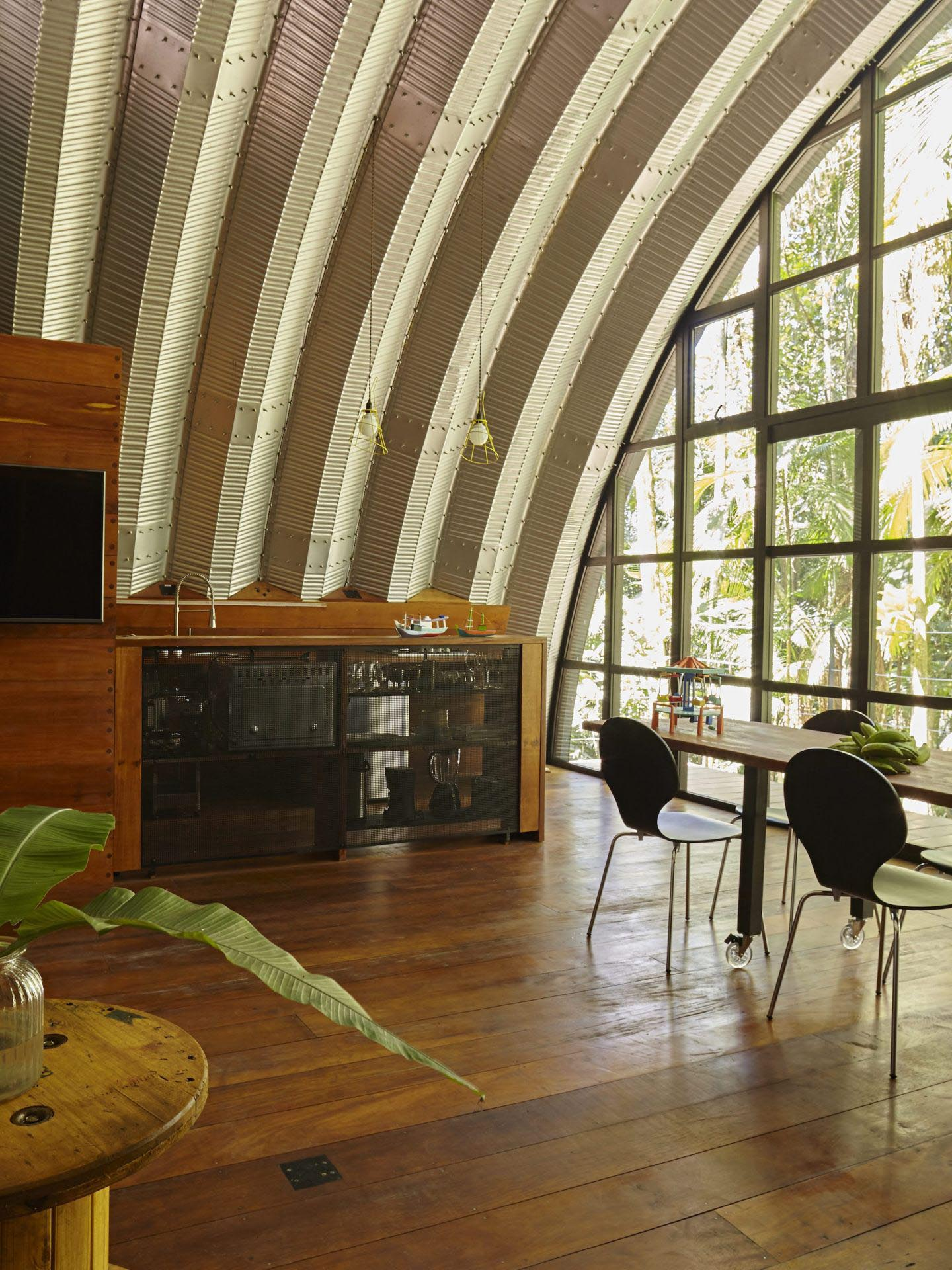 A modern home with an arched metal roof has a small kitchen, and a full wall of windows.
