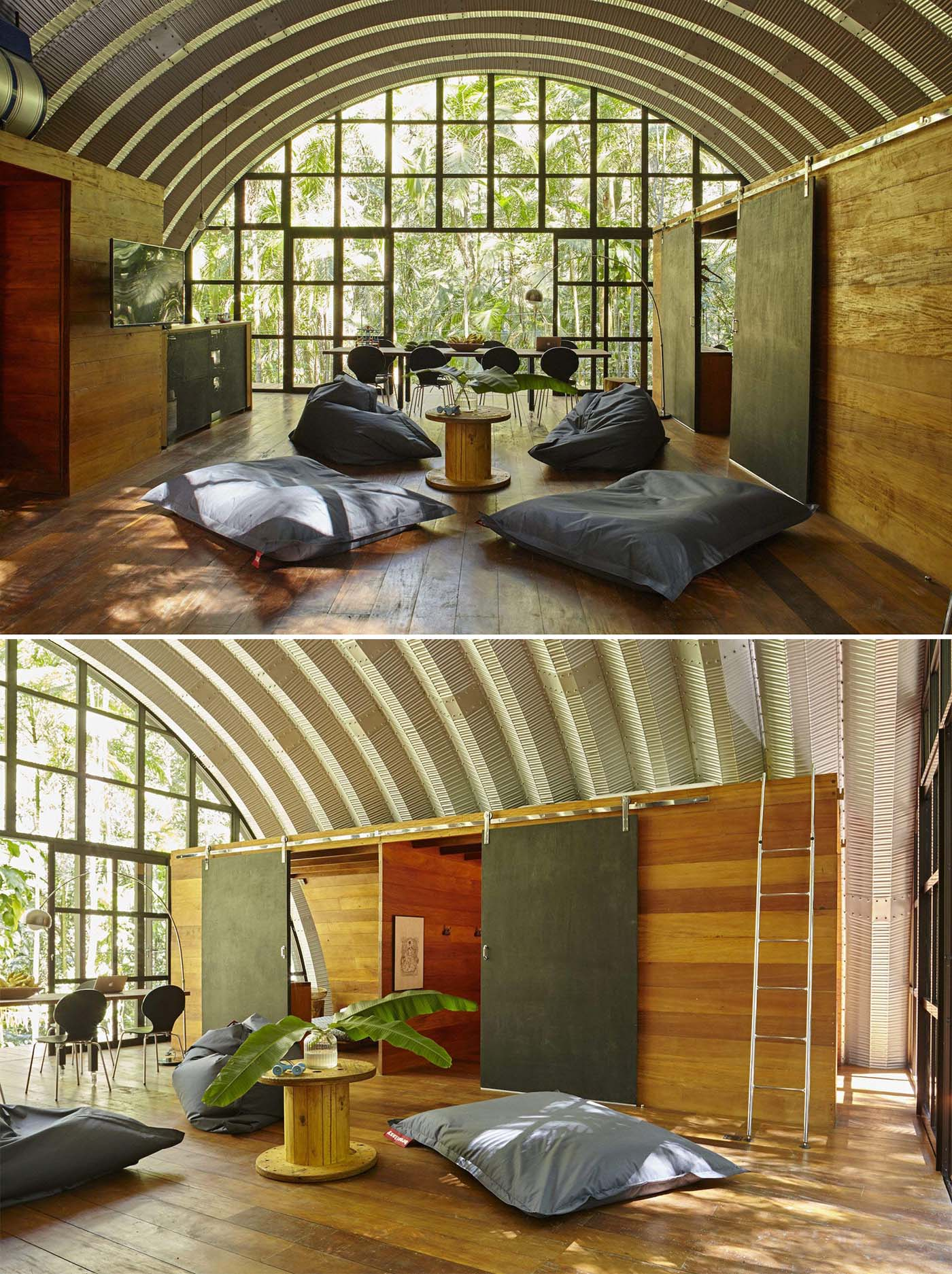 A modern home with an arched metal roof has an open floor plan, and a full wall of windows.