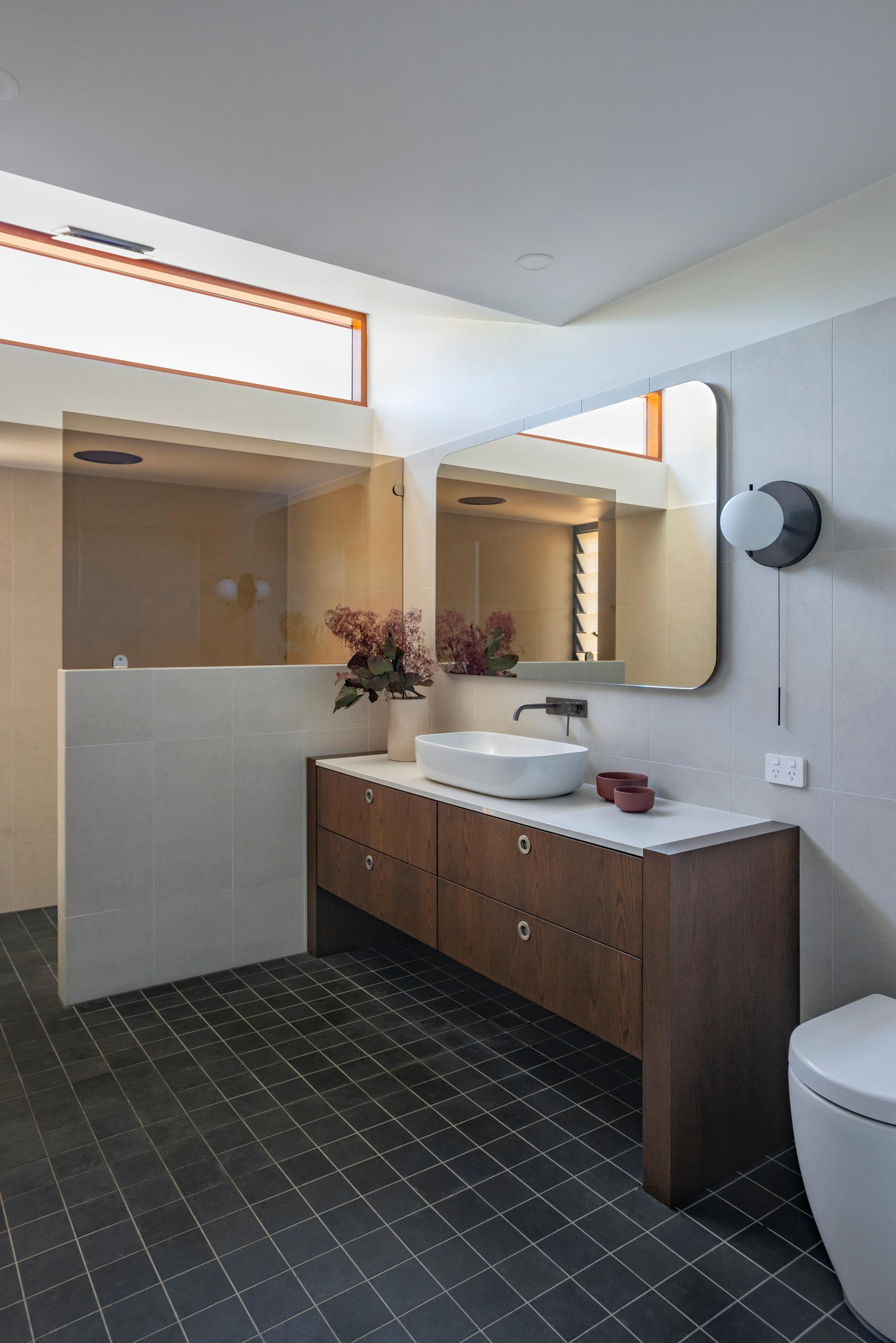 A modern bathroom with a dark wood vanity that's been paired with dark flooring and light colored walls.