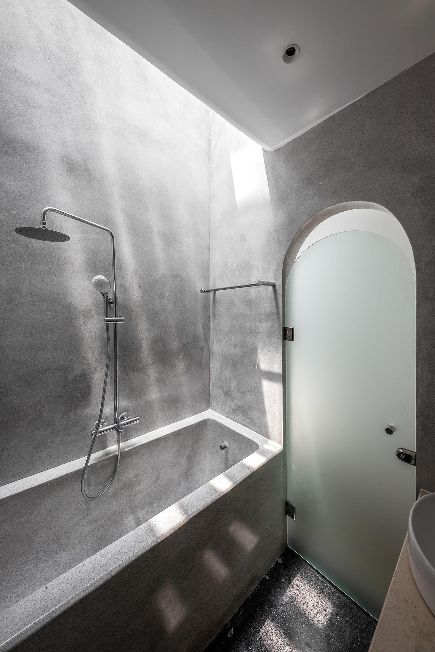 A modern grey bathroom with a frosted door, as well as a built-in bathtub.