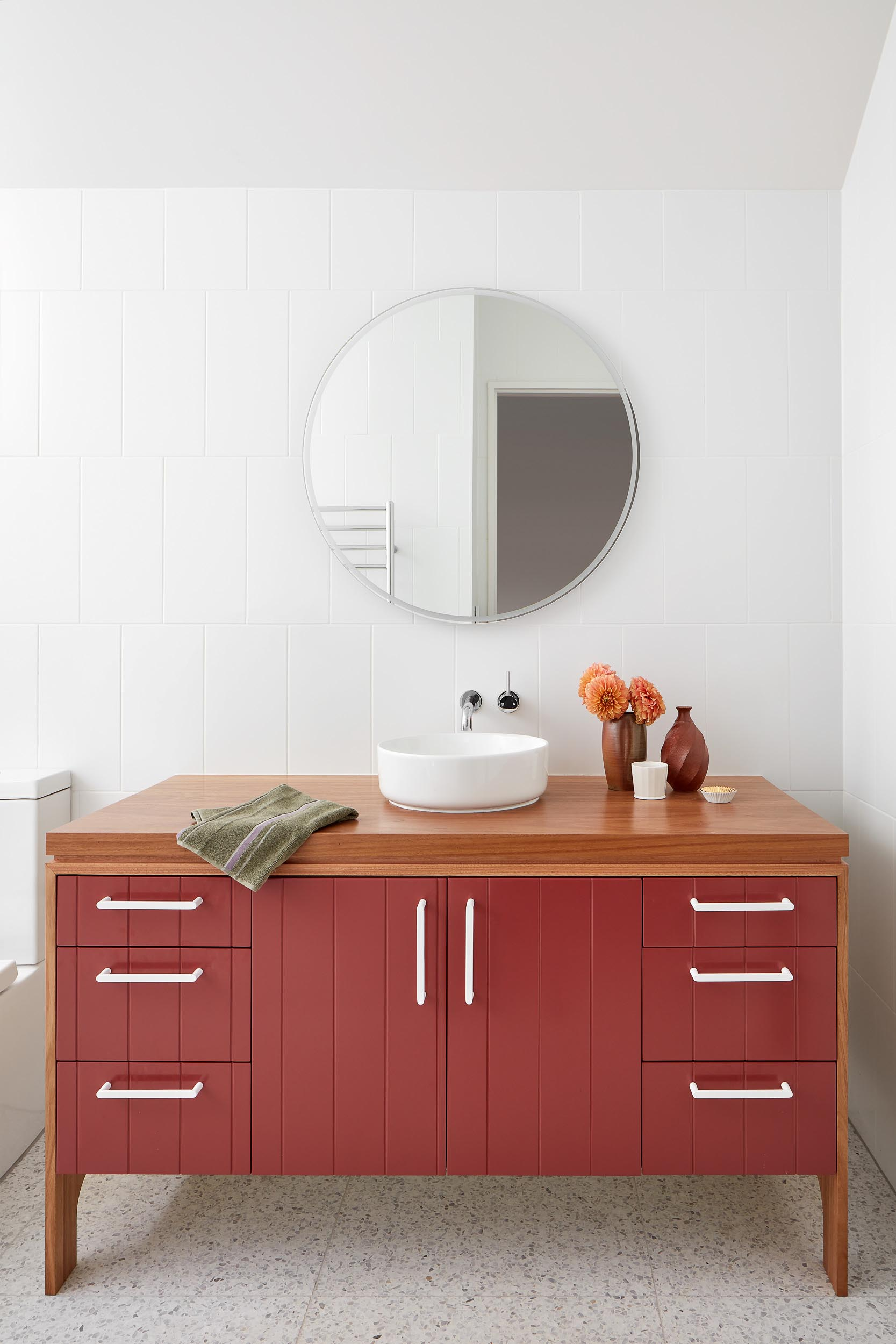 In this modern bathroom, the color for the room comes from the vanity that sits below a round mirror.