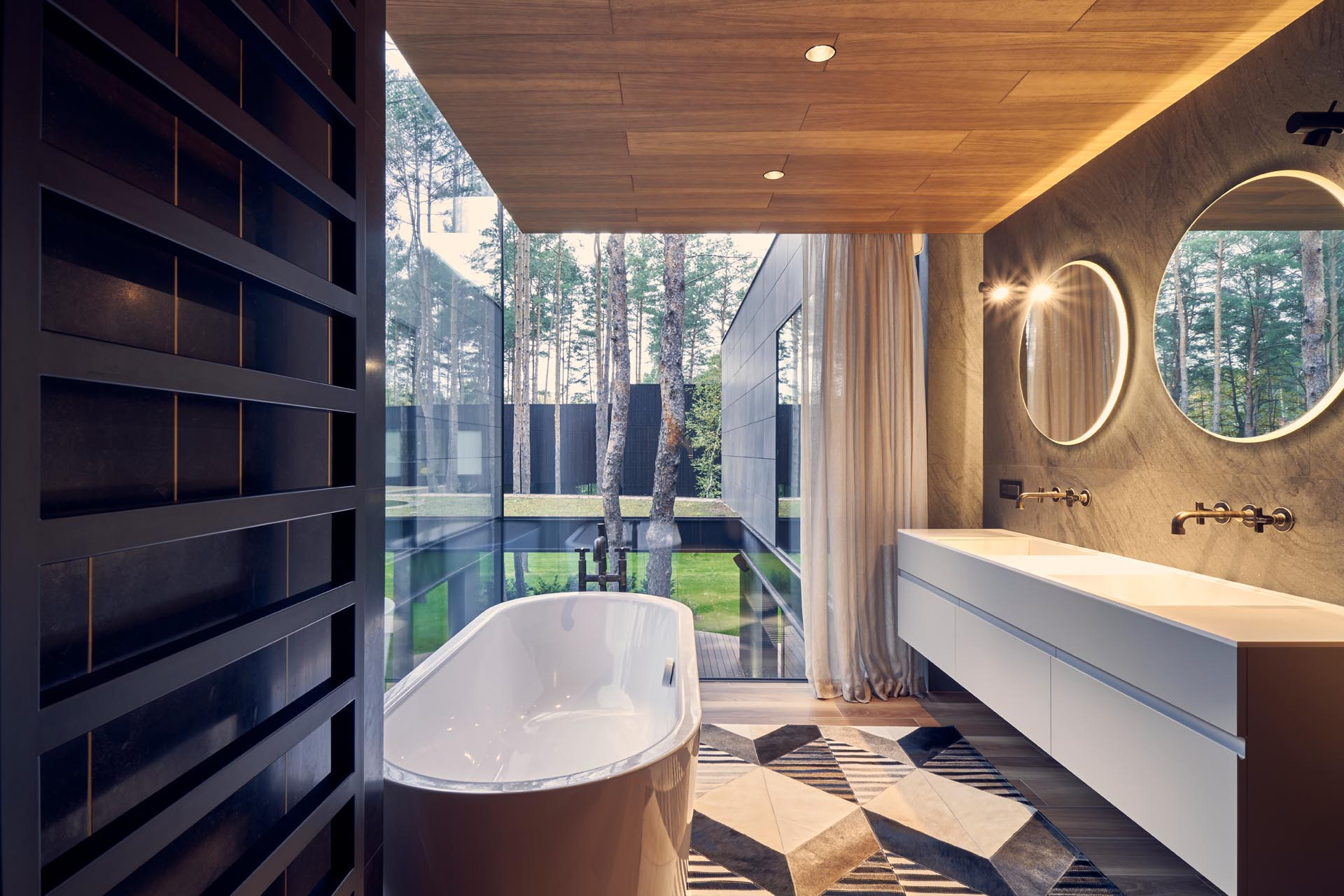 A modern bathroom with corner windows, round mirrors, a wood ceiling, and a floating white vanity with double sinks.