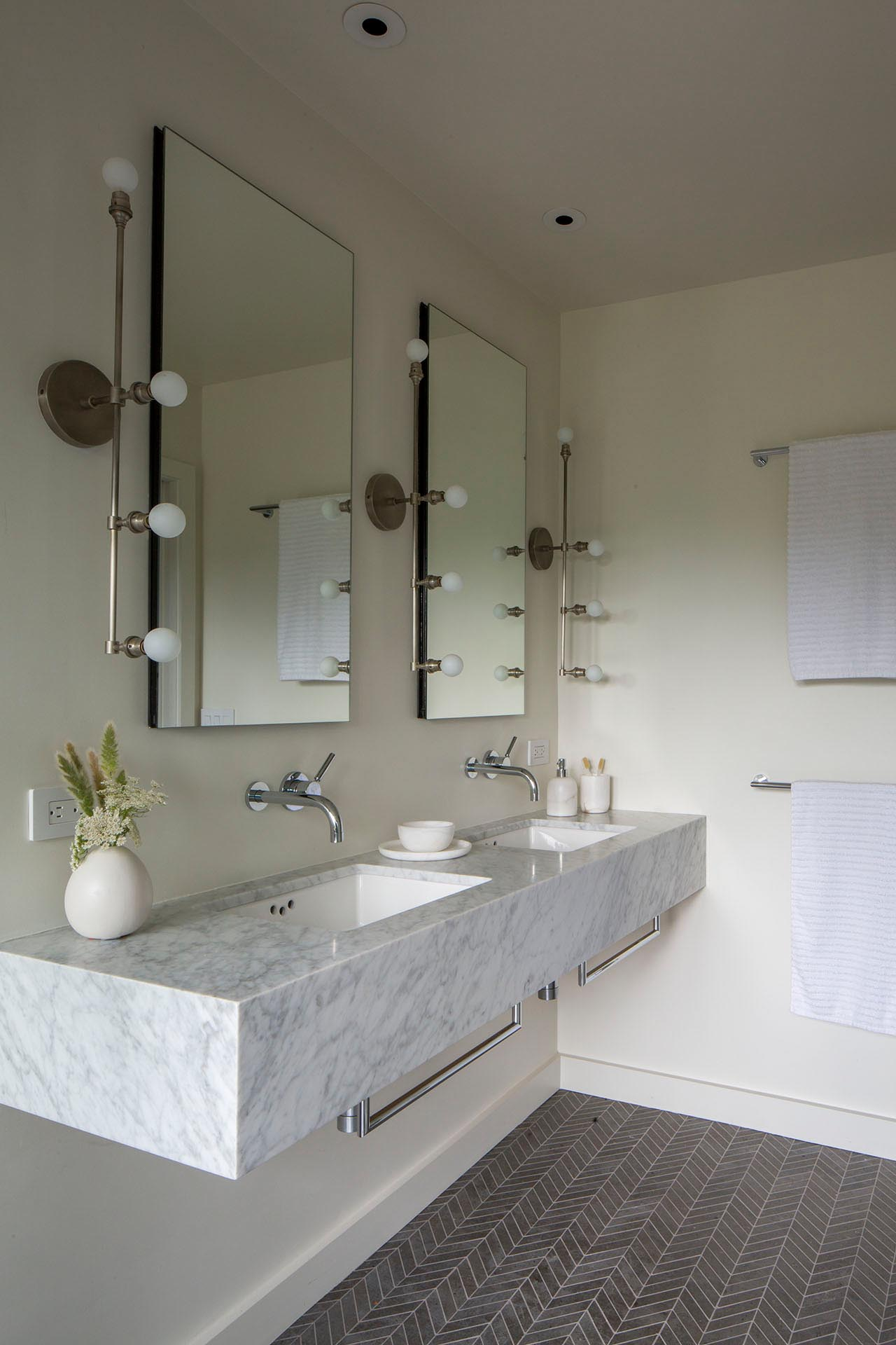 A modern bathroom with a floating vanity and patterned tile flooring.