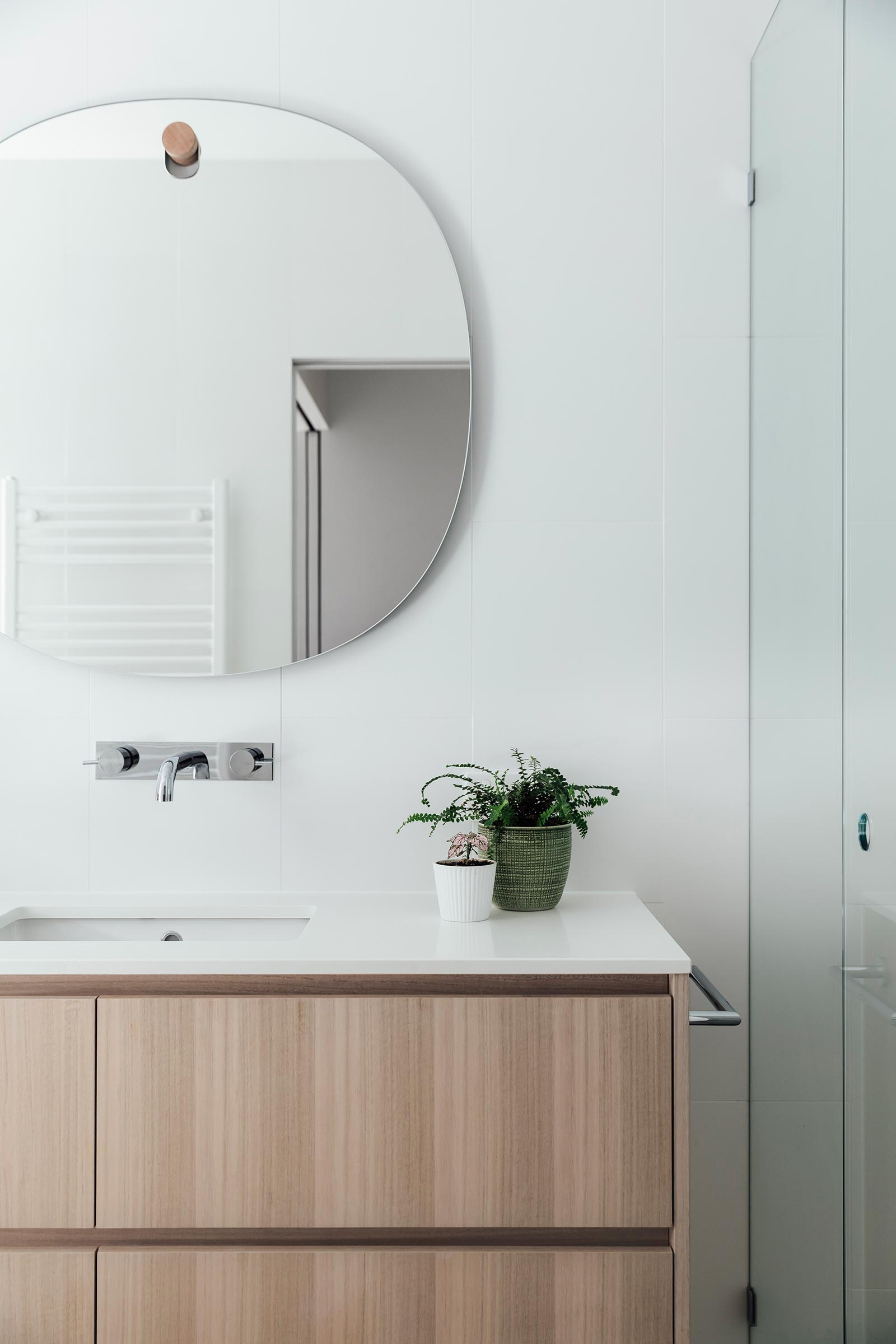 In this modern bathroom, while tiles cover the walls, while a rounded frameless mirror hangs from a simple wood hook, which also matches the wood vanity.