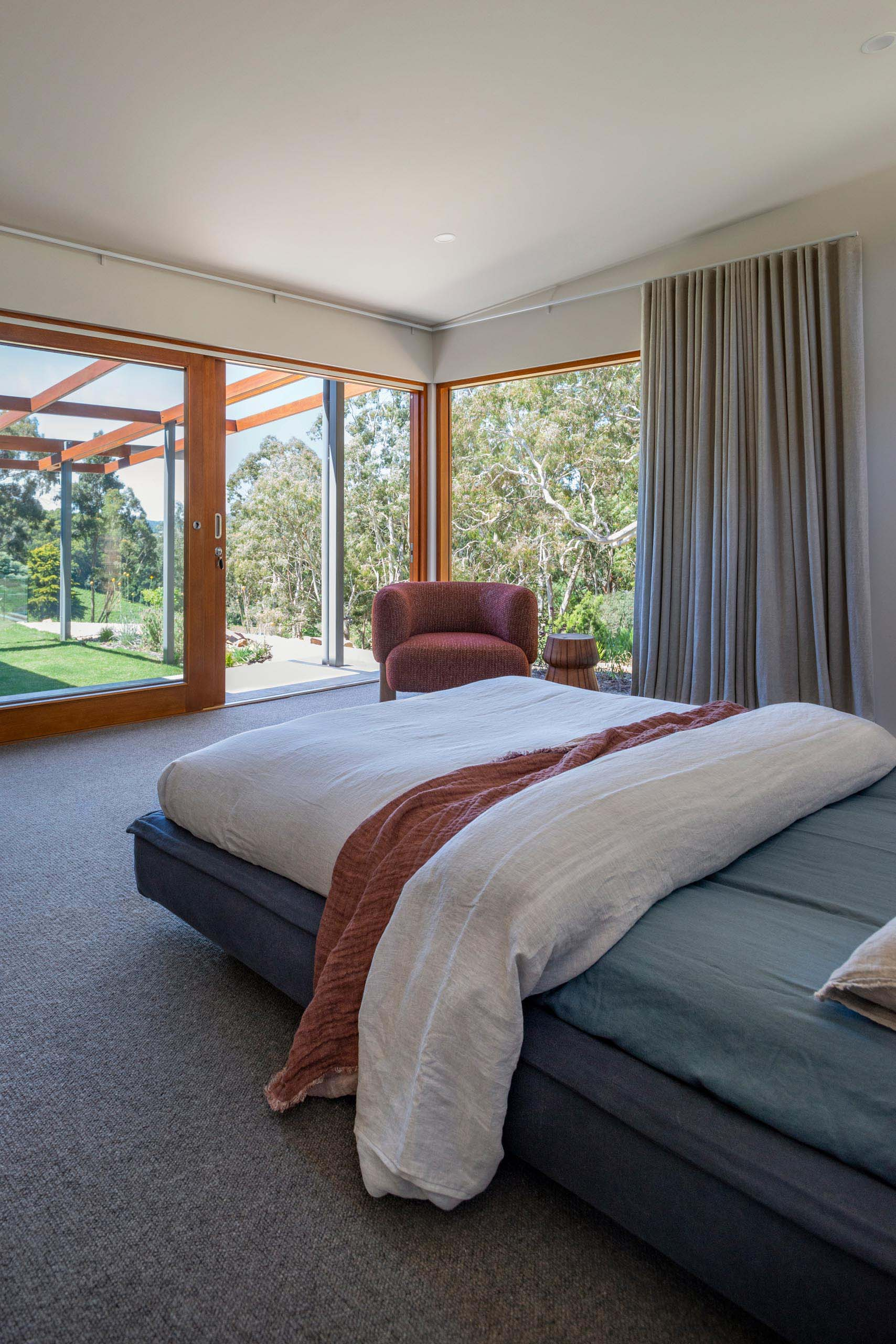 Large windows and a sliding door provide an uninterrupted tree view in a modern bedroom.