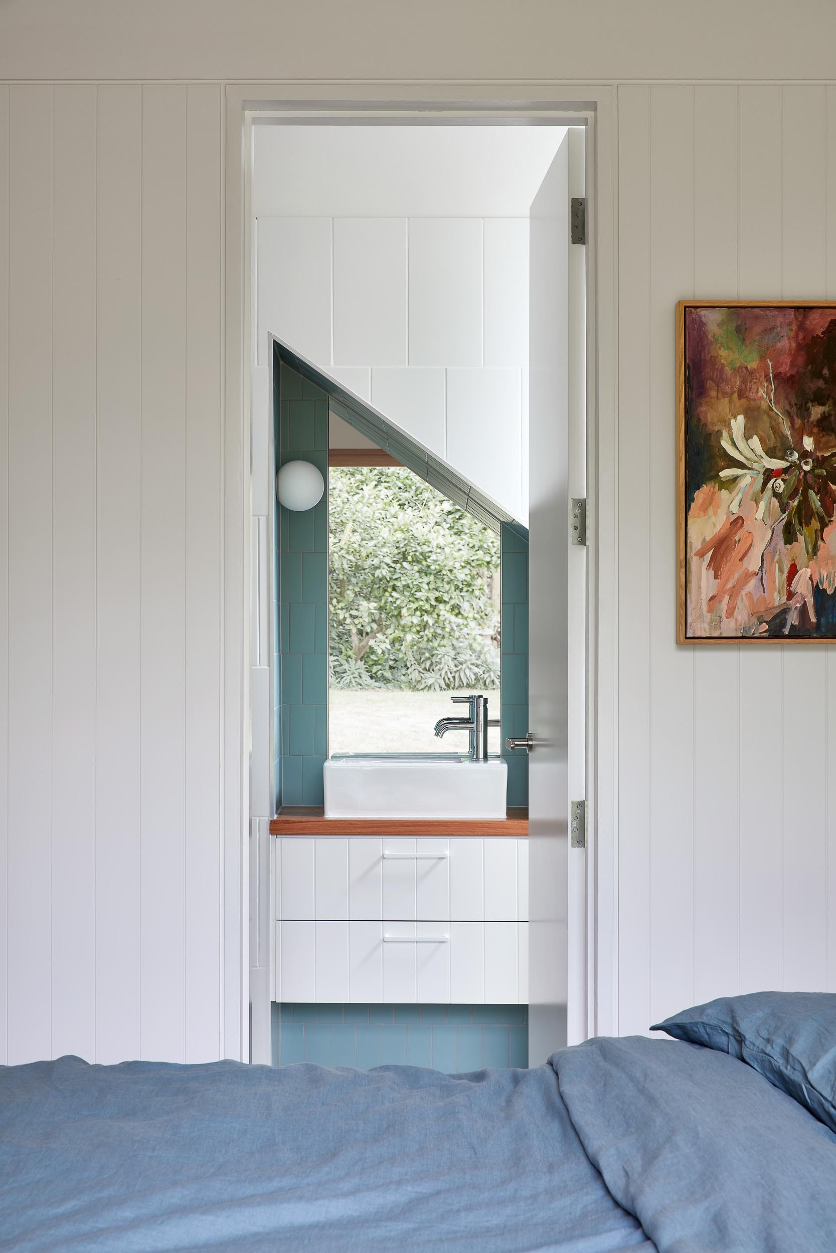 A modern bedroom has an en-suite bathroom with an angled mirror.