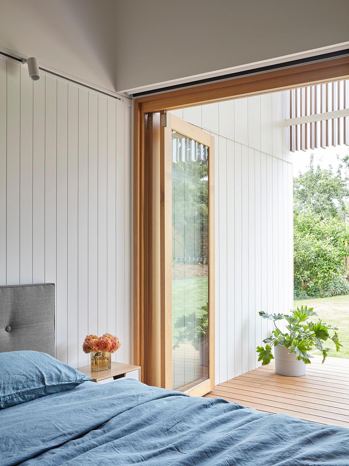 Folding wood framed glass doors open this modern bedroom with textured walls to the deck outside.
