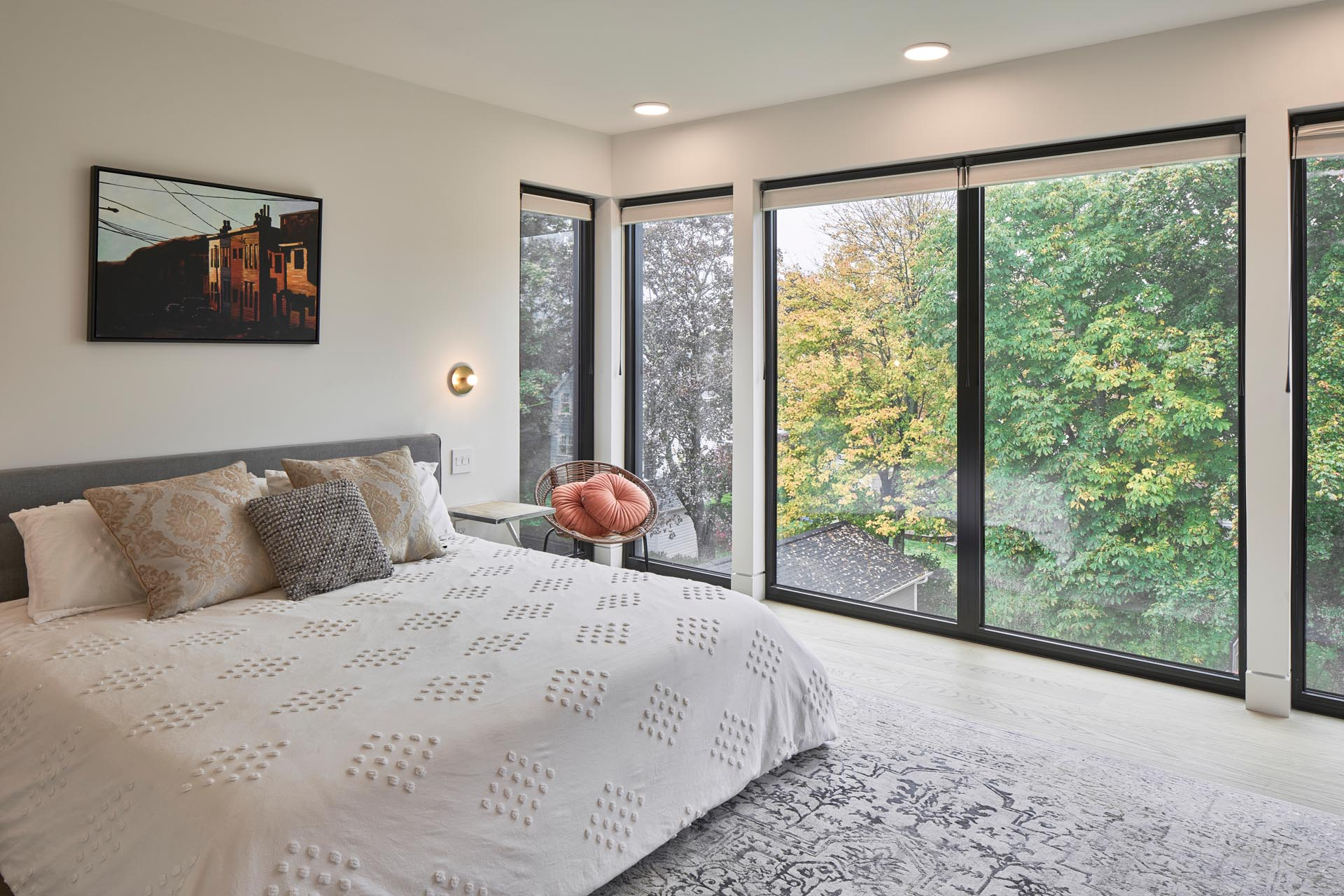 A modern bedroom with large black-framed windows that showcase the greenery outside.