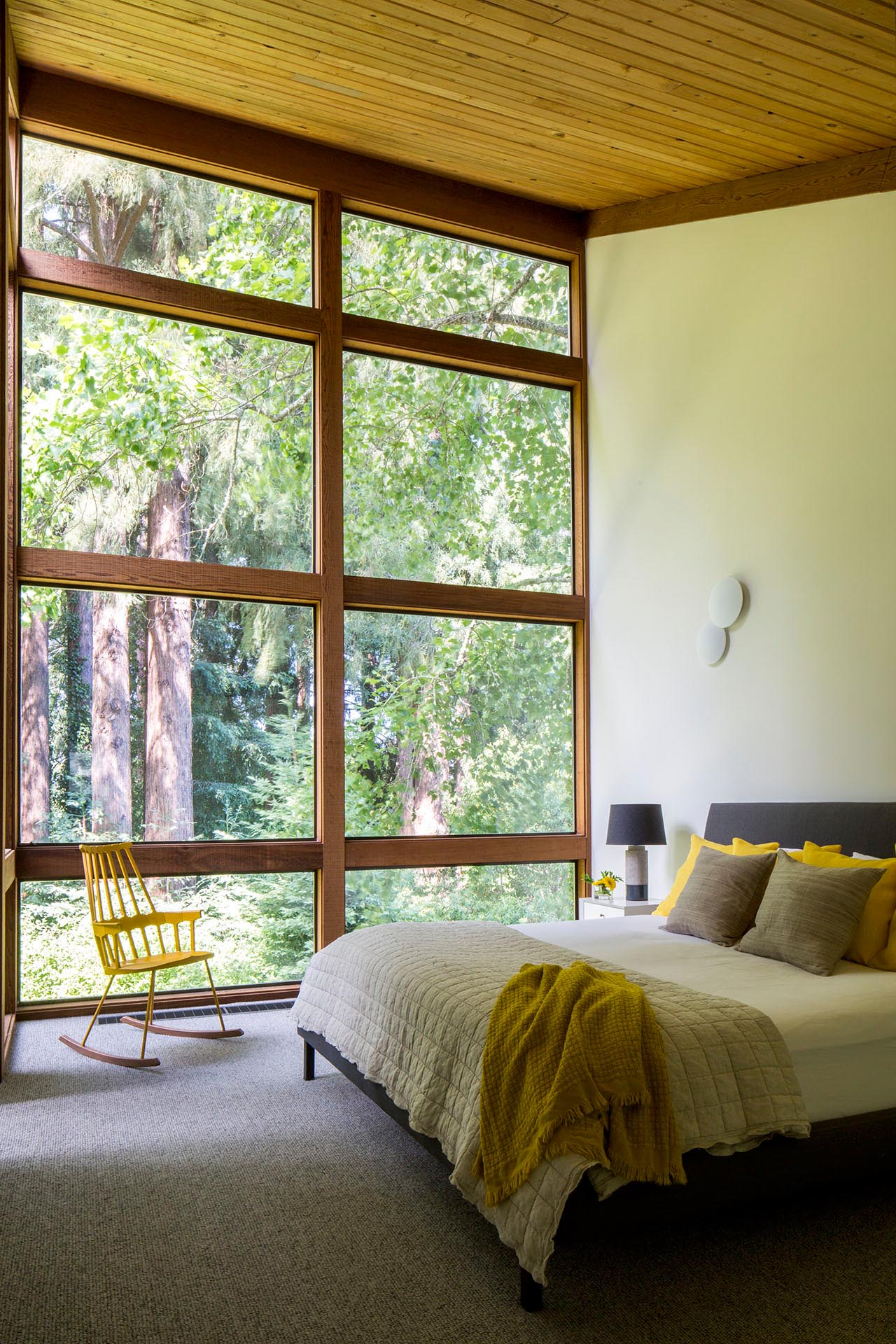A modern bedroom with high ceilings and a wall of wood-framed windows.