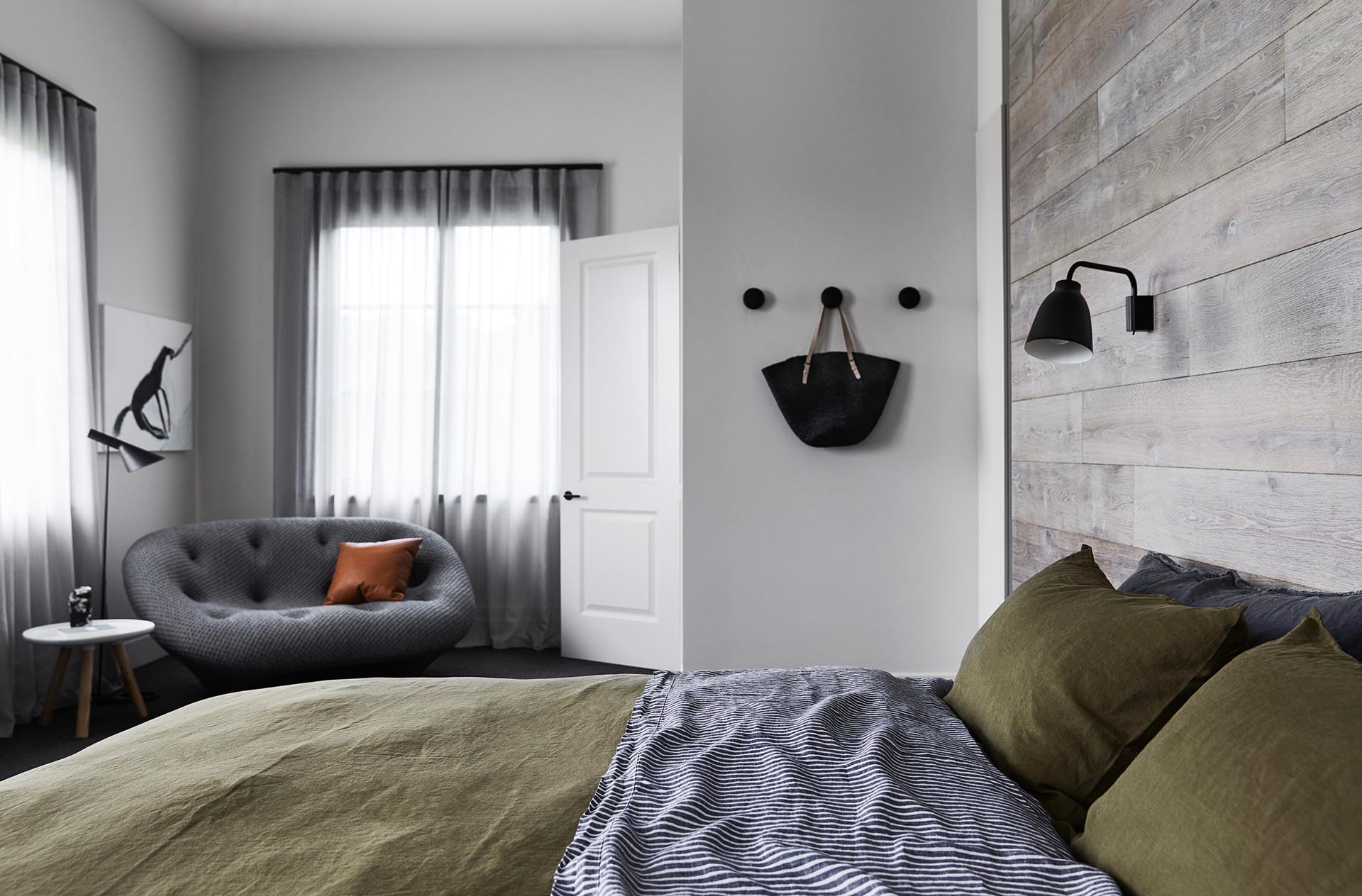 A modern farmhouse inspired bedroom with a French Oak wood accent wall.