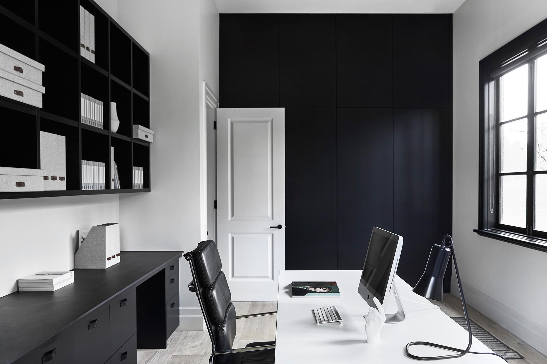This modern home office has been kept minimally furnished with the black joinery complementing the black window frames.