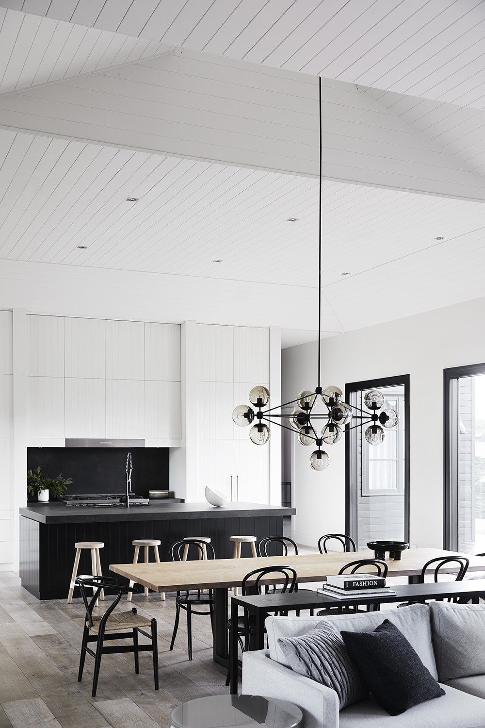 A modern farmhouse interior where the dining room is positioned between the living room and kitchen, all of which are open plan.