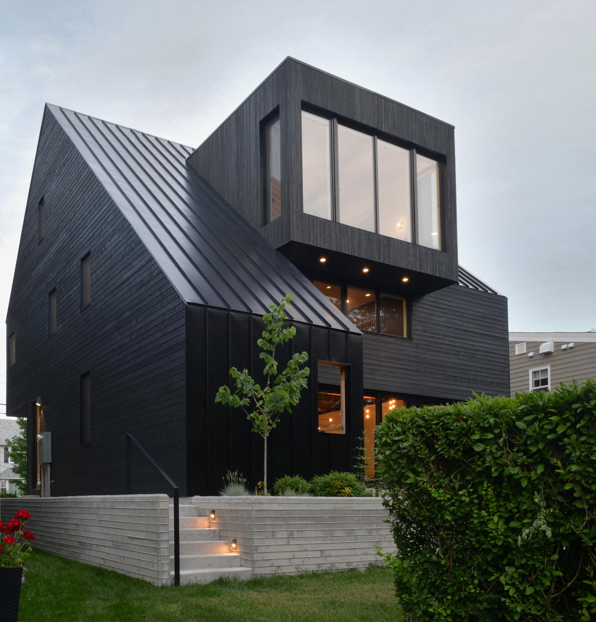 A modern black house with wood siding and a standing seam metal roof.