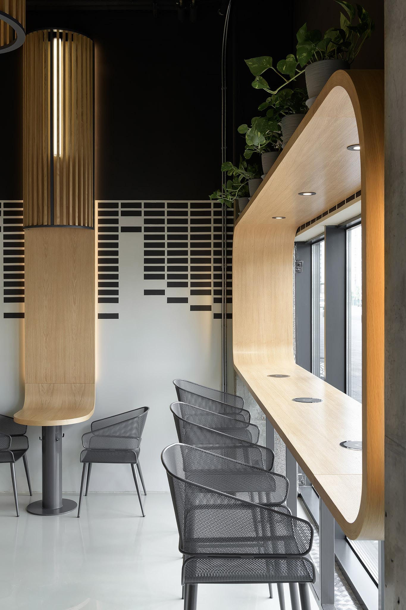 A modern coffee shop with wood-lined window seating.