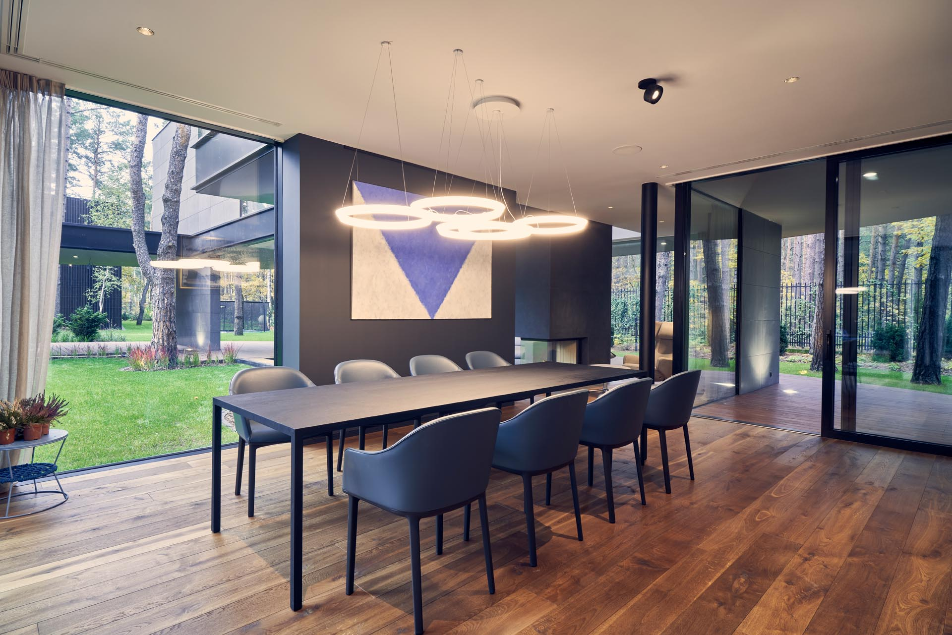 A modern dining room with floor-to-ceiling windows and warm wood floors.