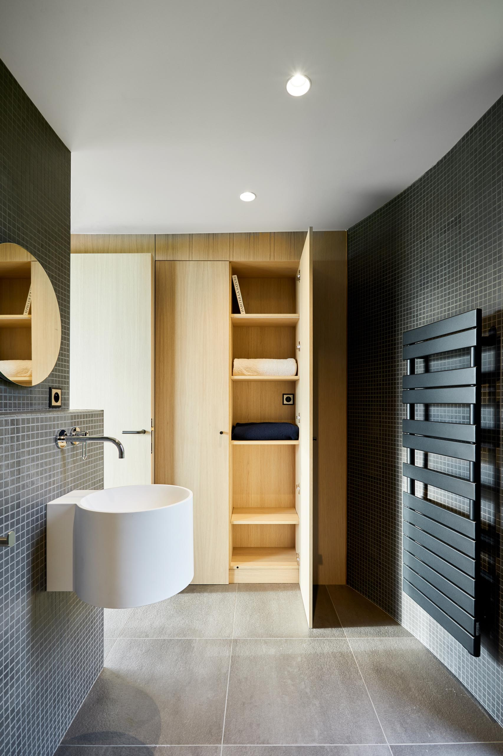 A modern bathroom with walls covered in small square grey tiles.