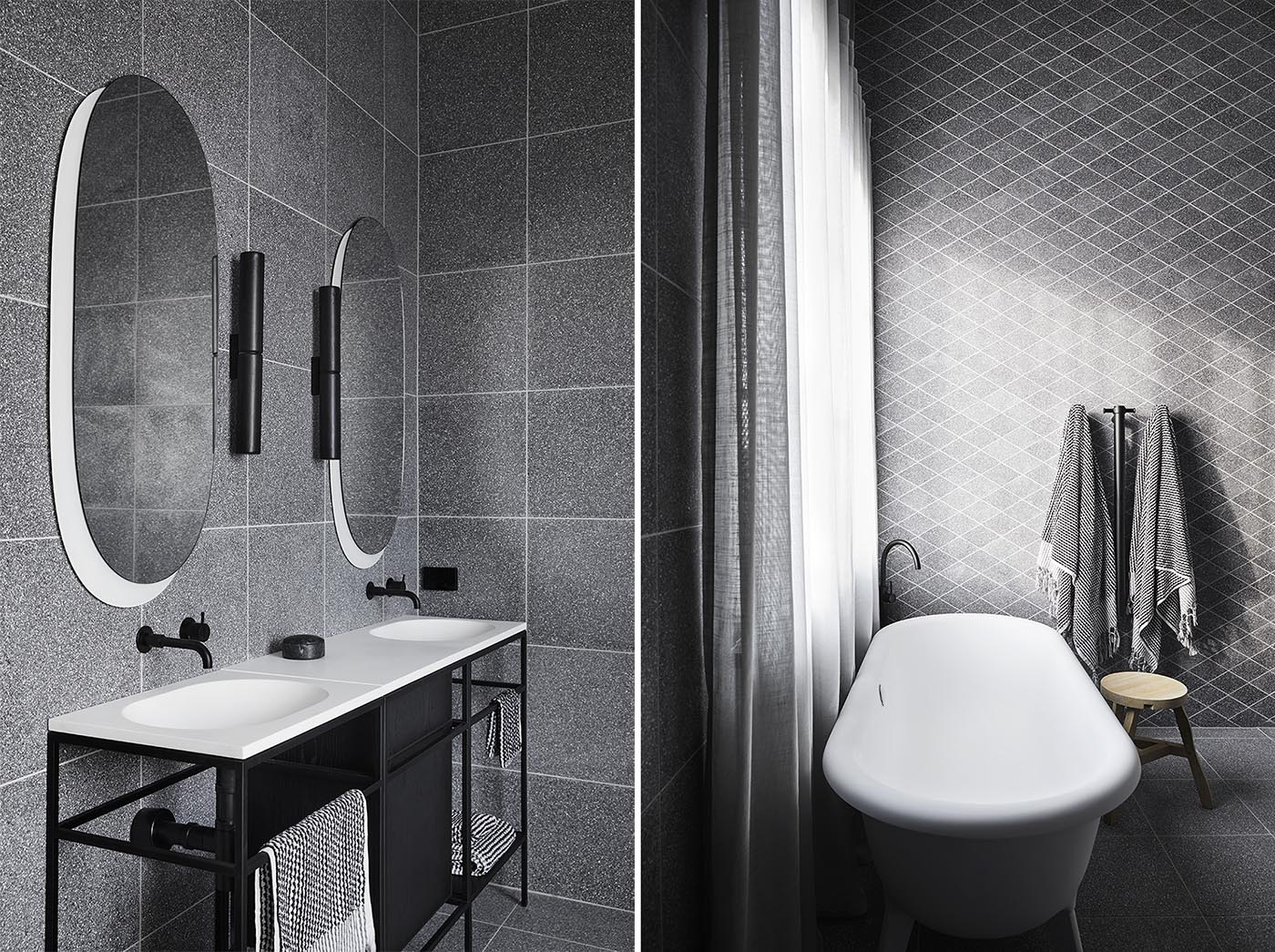 Modern grey and black bathrooms with terrazzo tile covered walls.
