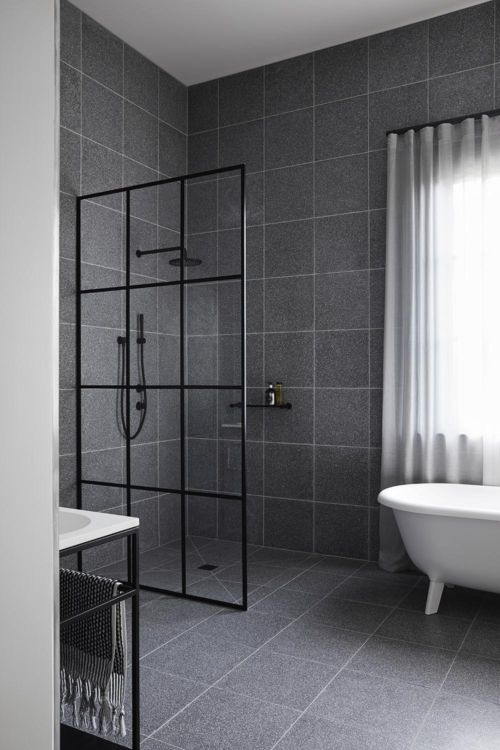 Modern grey and black bathroom with terrazzo tile covered walls, and a black framed glass shower screen.