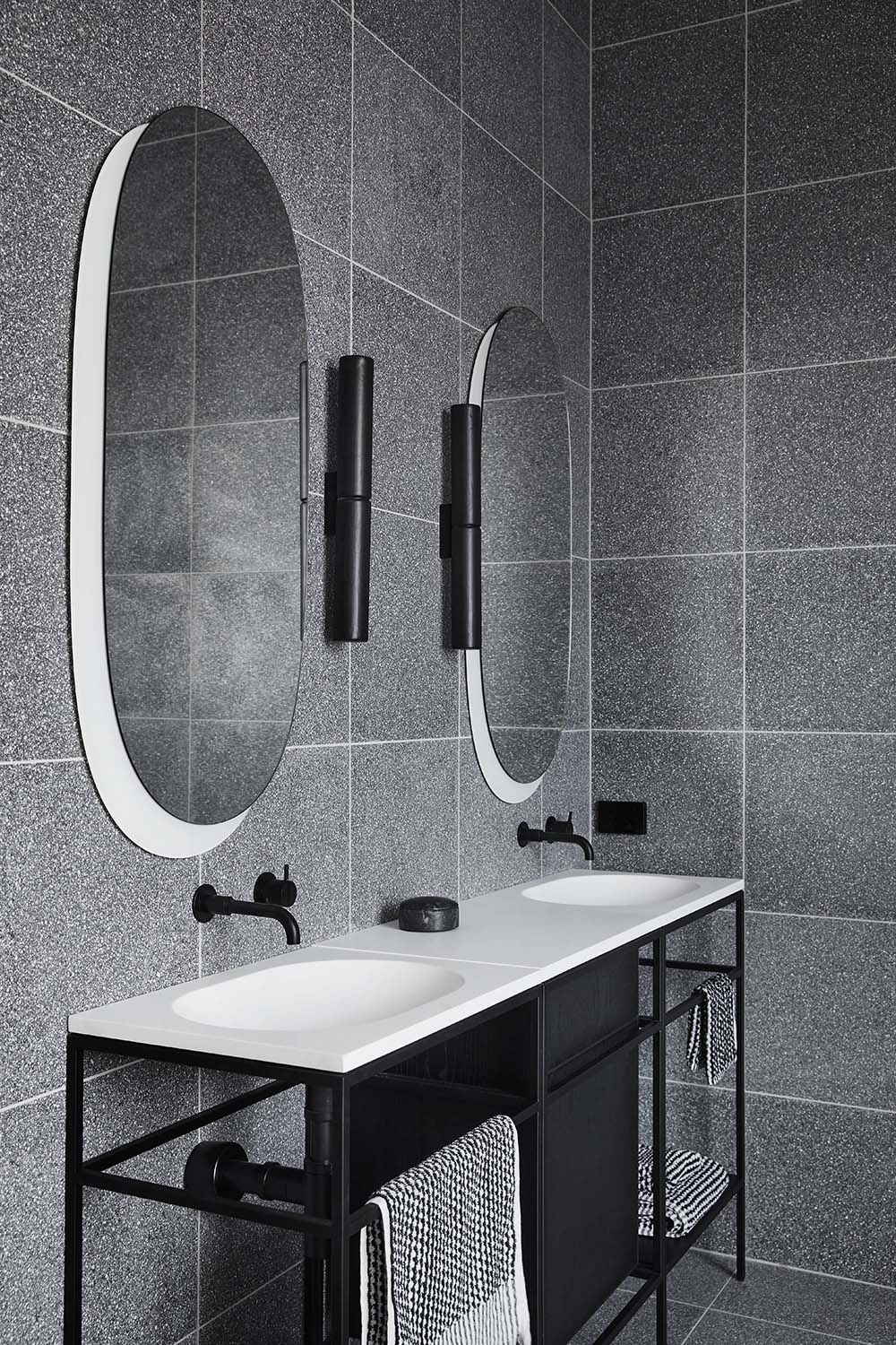 The extremely minimalist and slimline consoles by Ex.t, have black steel frames with white countertops and integrated basins, adding a lightness to the otherwise dark bathrooms.