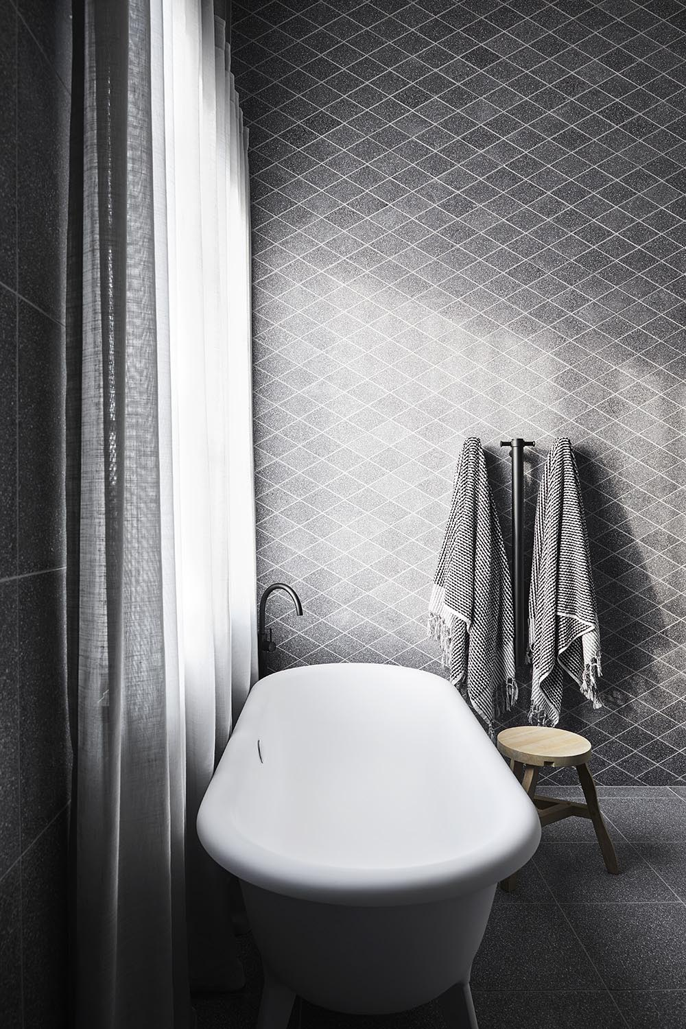 This modern main en-suite bathroom features a wall of custom diamond-cut terrazzo, a geometric shift designed to surprise and relieve the eye, while the Ottocento bath by Agape rests below the window.