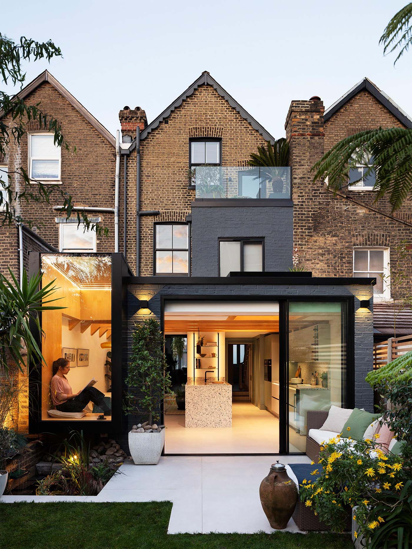 A side and rear extension for a Victorian mid-terrace house in London, England, that includes a window seat and an internal courtyard.