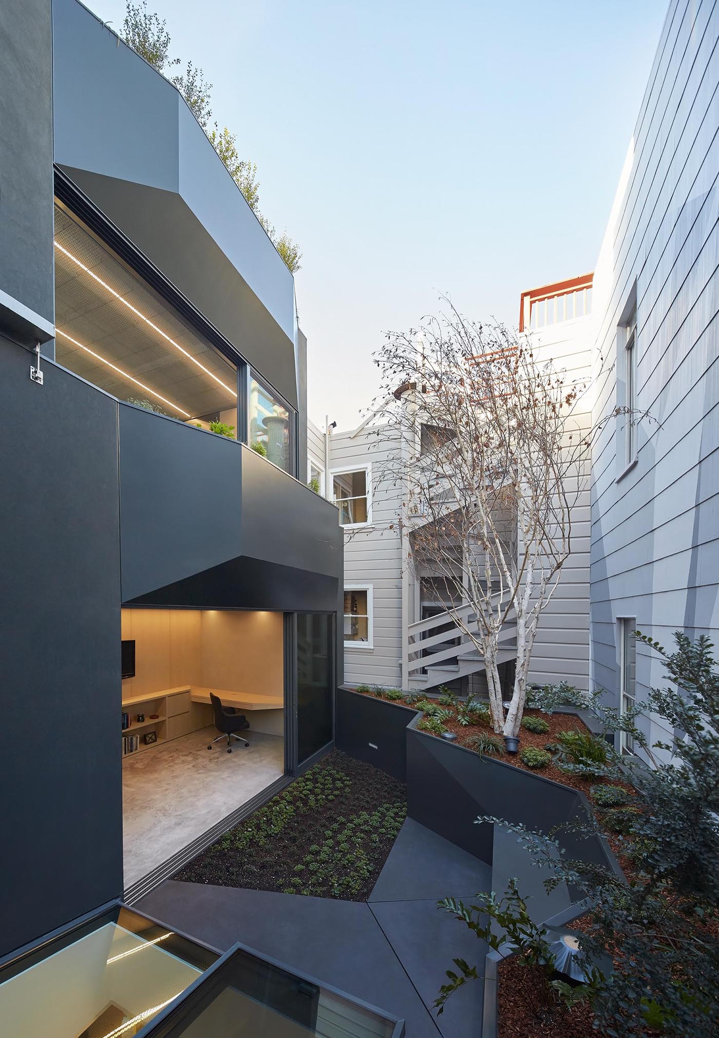 A modern home with a small rear garden that raised up creating room for a built-in bench.