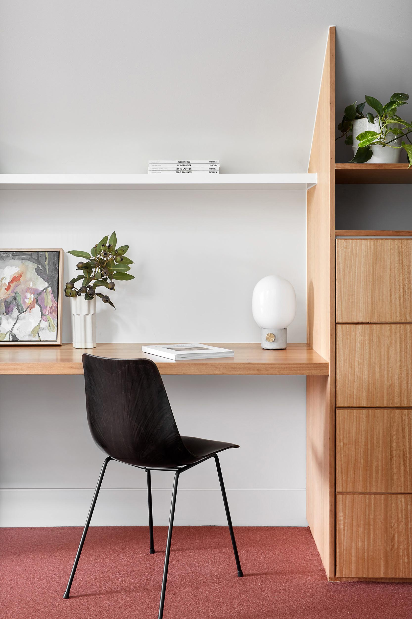A home office includes colorful carpet, a custom designed desk and cabinets, and a white shelf.