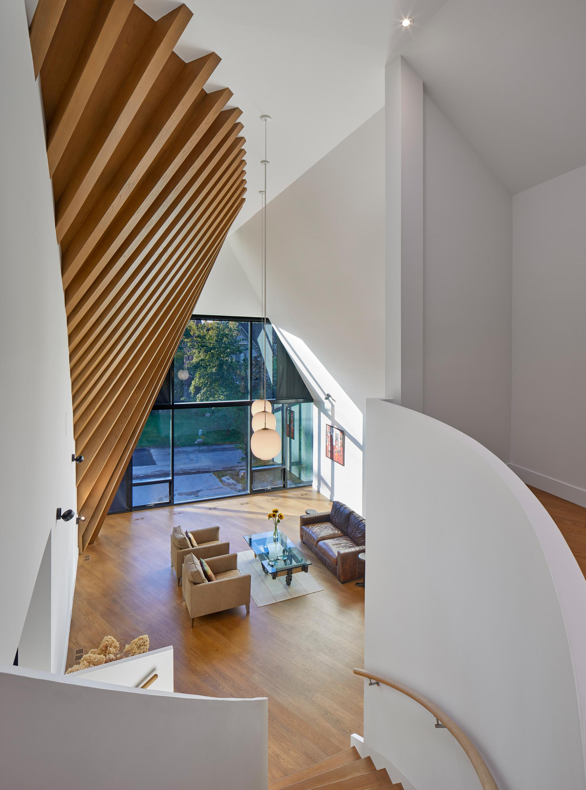A modern home interior with exposed rafters clad with red oak veneer continue the roof's dynamic shape.