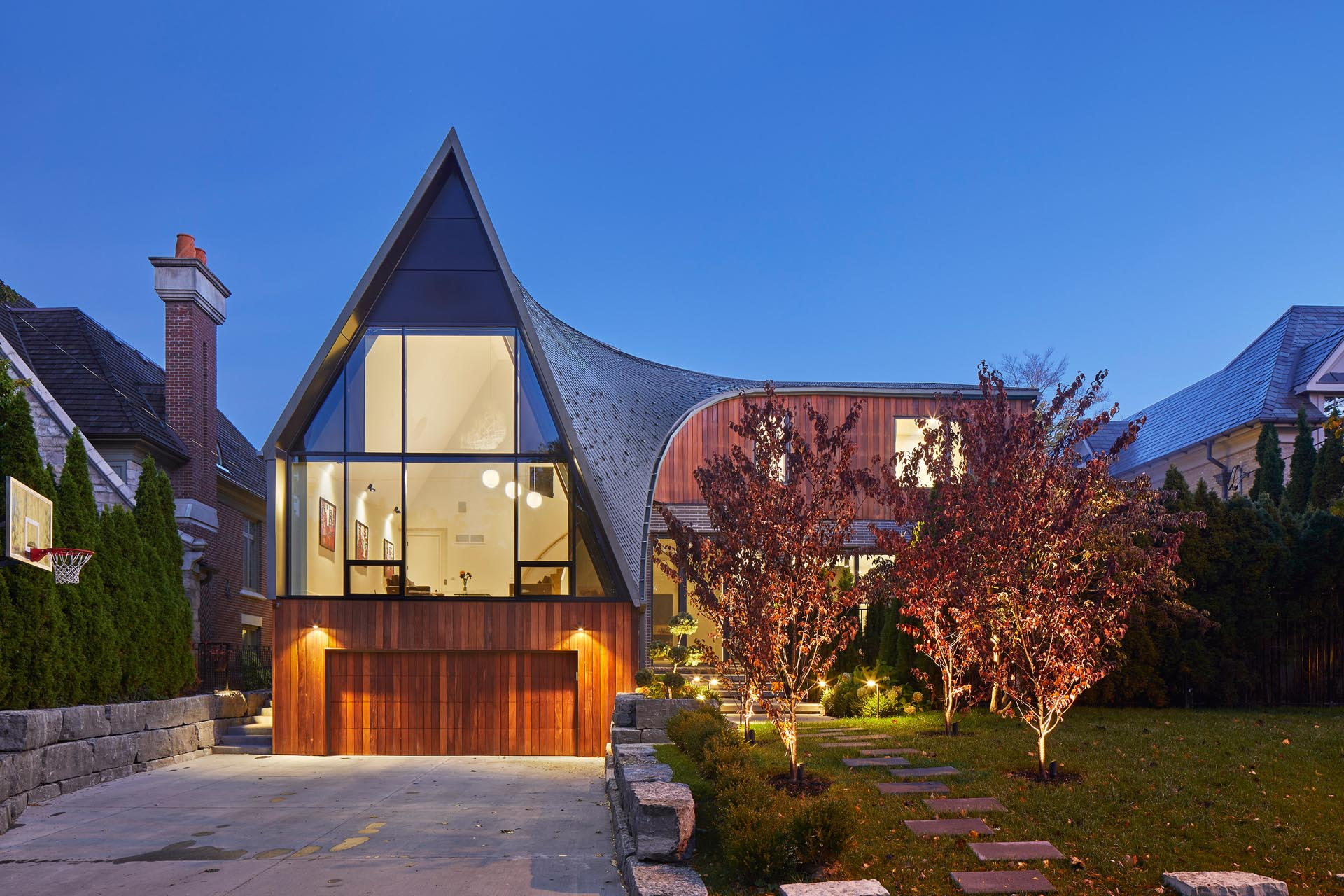 A modern home with a curved roof, an L-shaped design, and a A-frame accent.