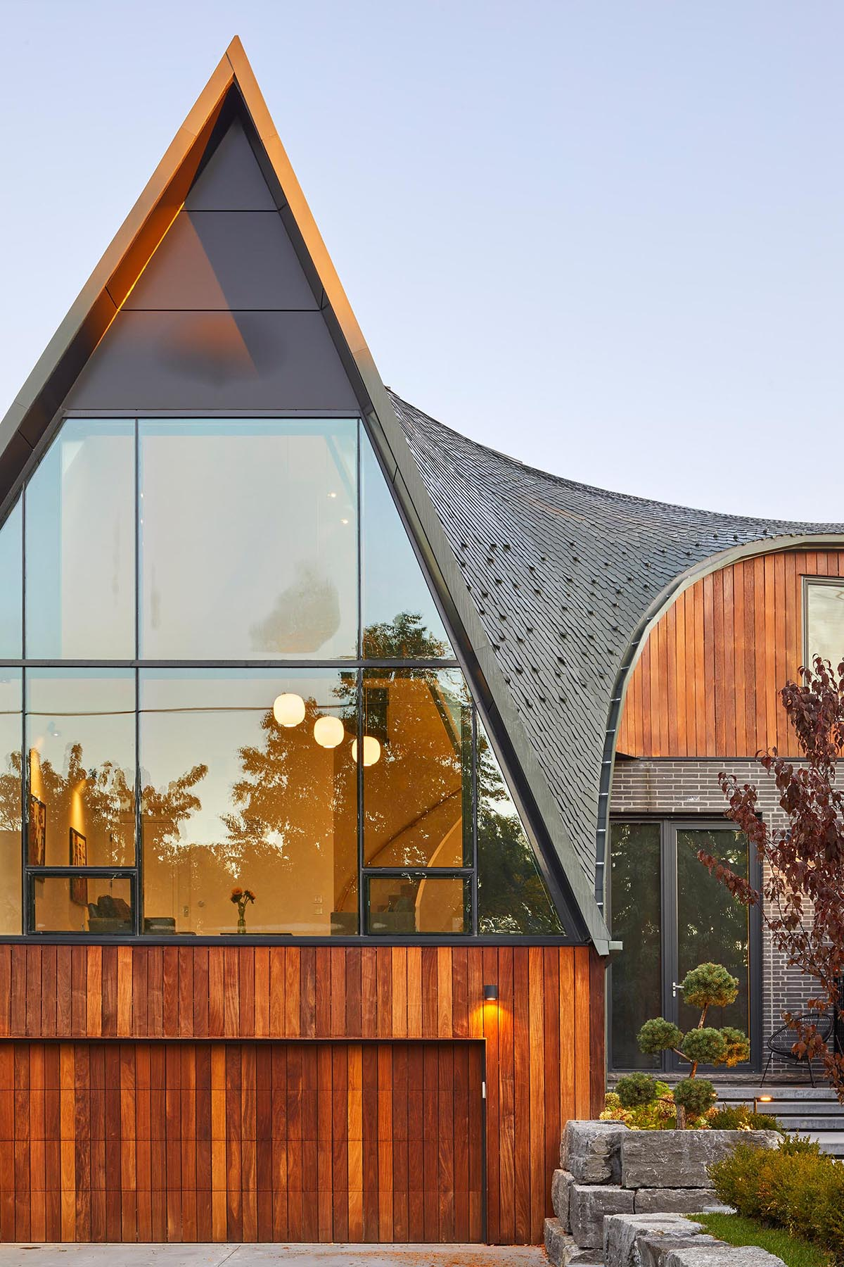 The facade of this modern home with a curved roof features Ipe and brick, that establish a contemporary palette that compliments the neighboring stone, brick and wood homes.