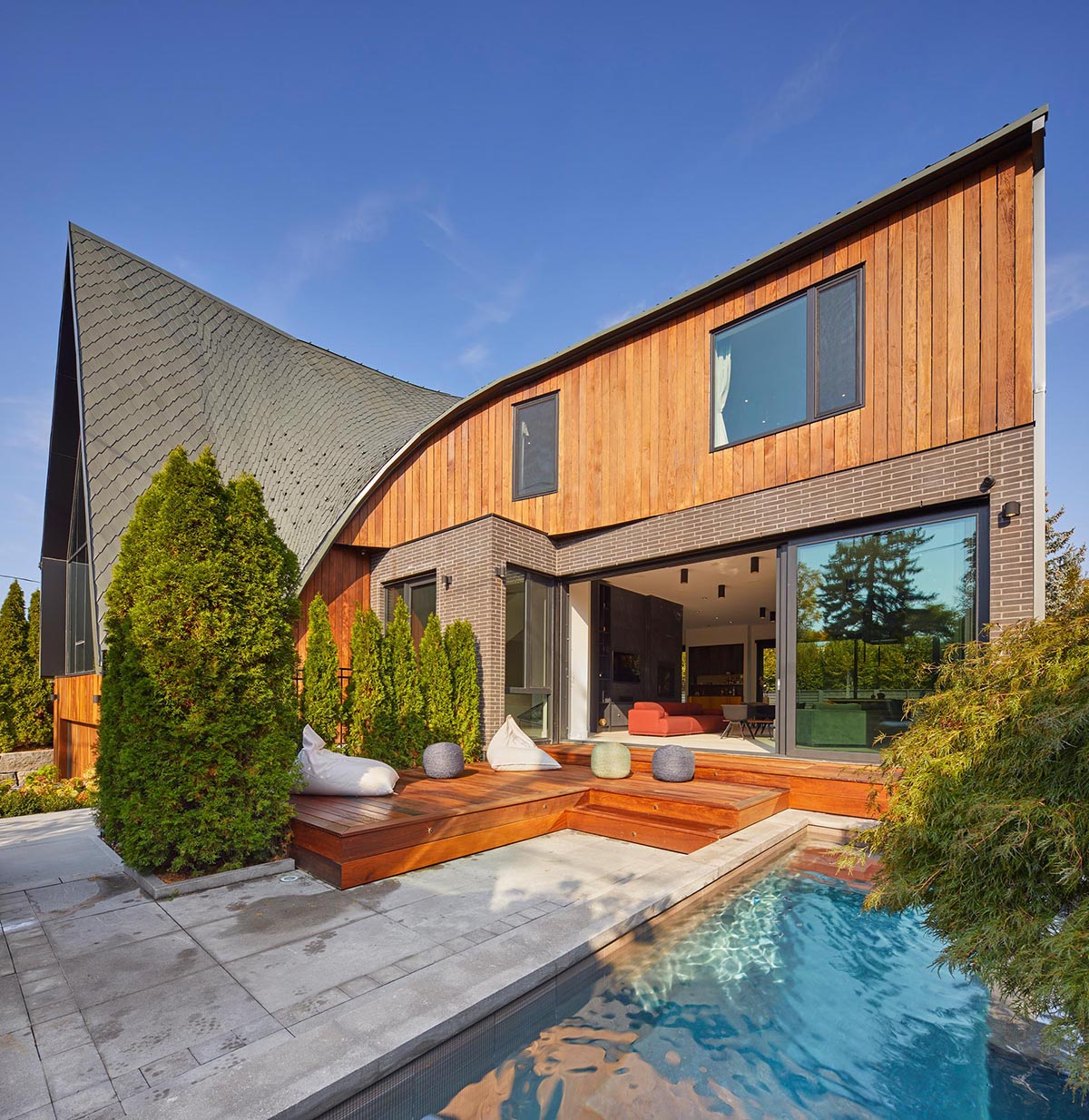 A modern home with a curved roof has a small front courtyard with a swimming pool and sun deck.