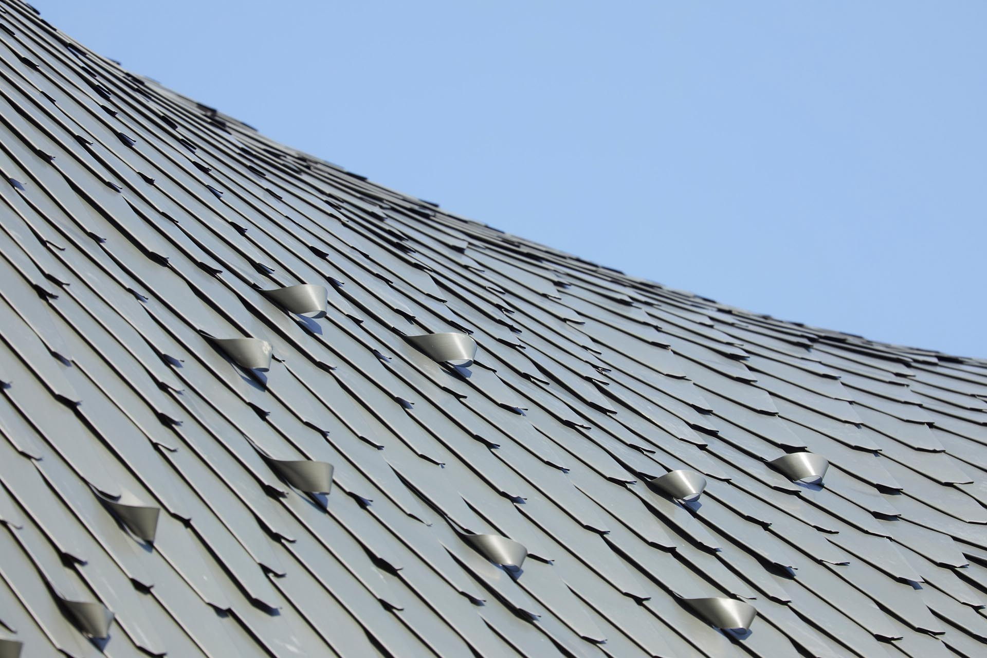 A modern curved roof is clad with hand-laid, diamond-shaped zinc shingles that both recalls a shimmering reptilian while also drawing connections with neighboring slate roofs. The handcrafted twisted zinc snow guards prevent falling snow.