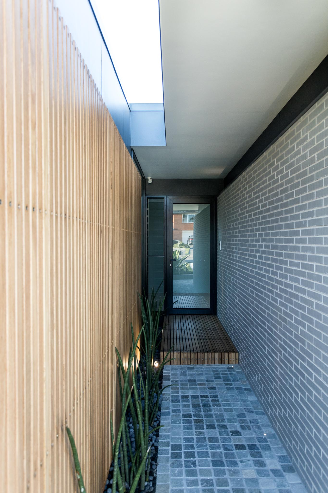 The covered entryway to this modern home is sandwiched between the wood slat wall and the new gray brick wall.