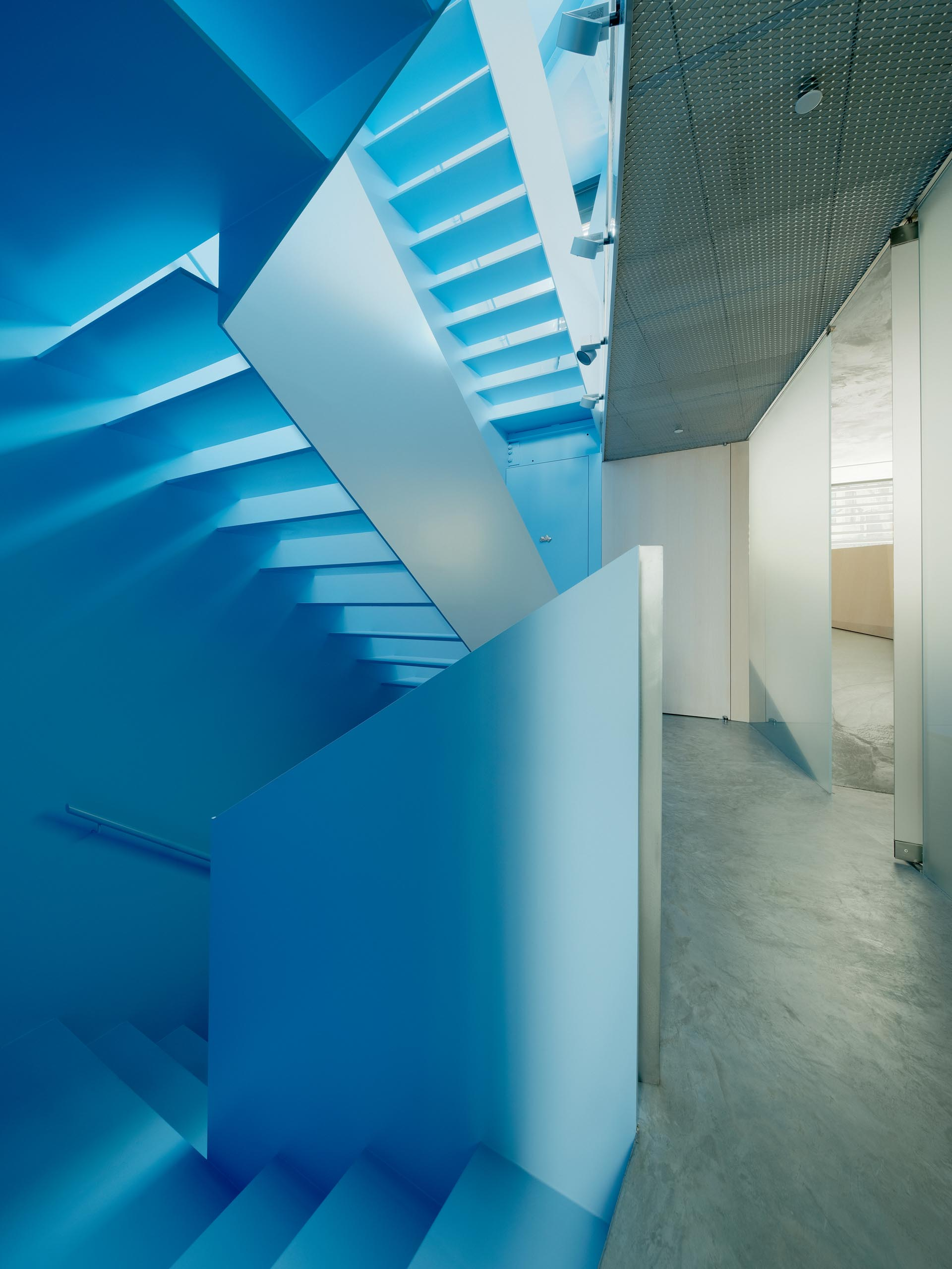 A modern house interior with a pastel blue staircase.