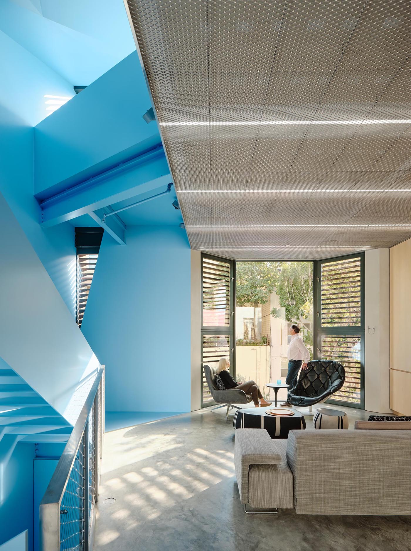 A modern home with a pastel blue staircase, and a living room with a high ceiling and bay window.