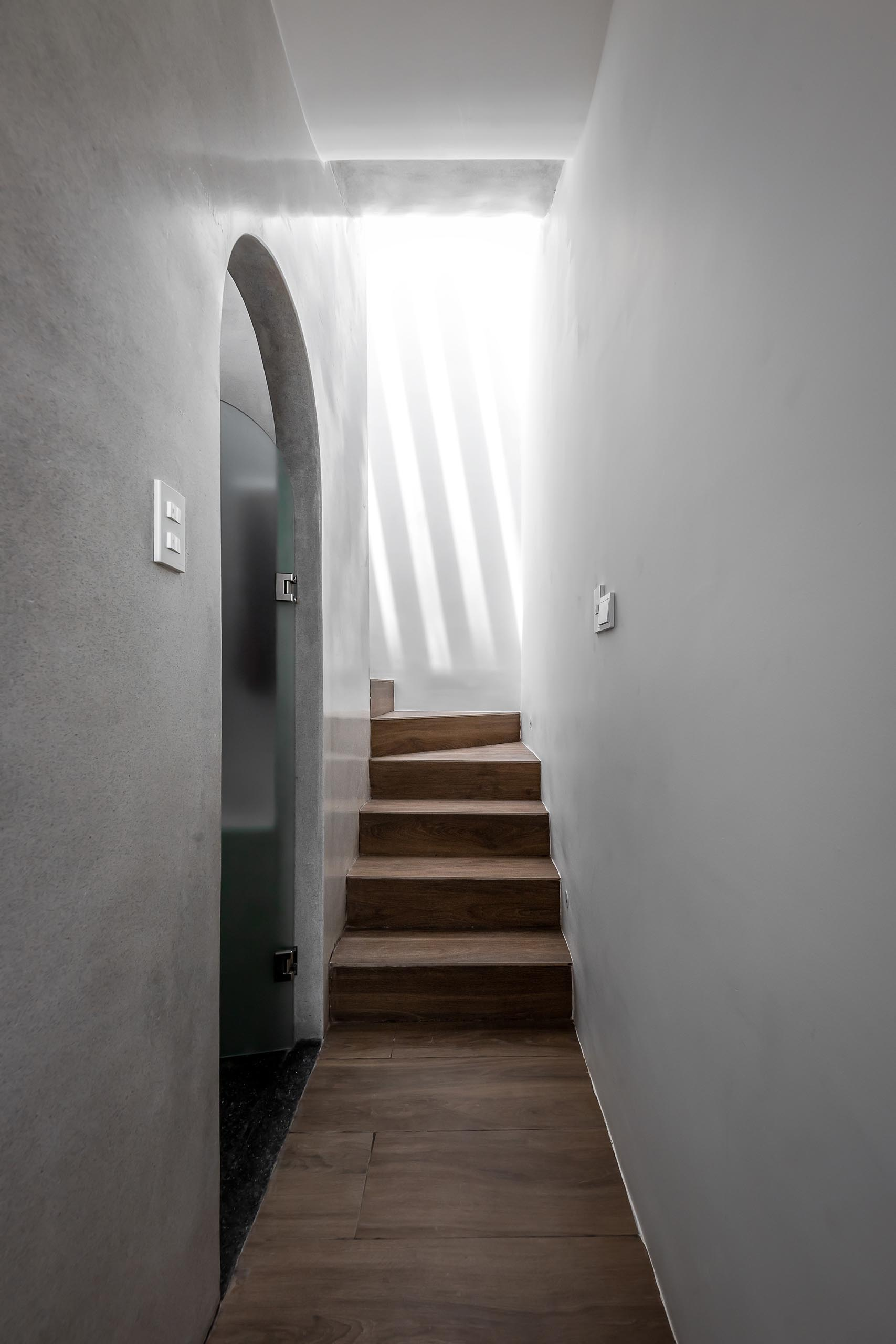 A modern home with stairs that are lit by skylights and spotlights.