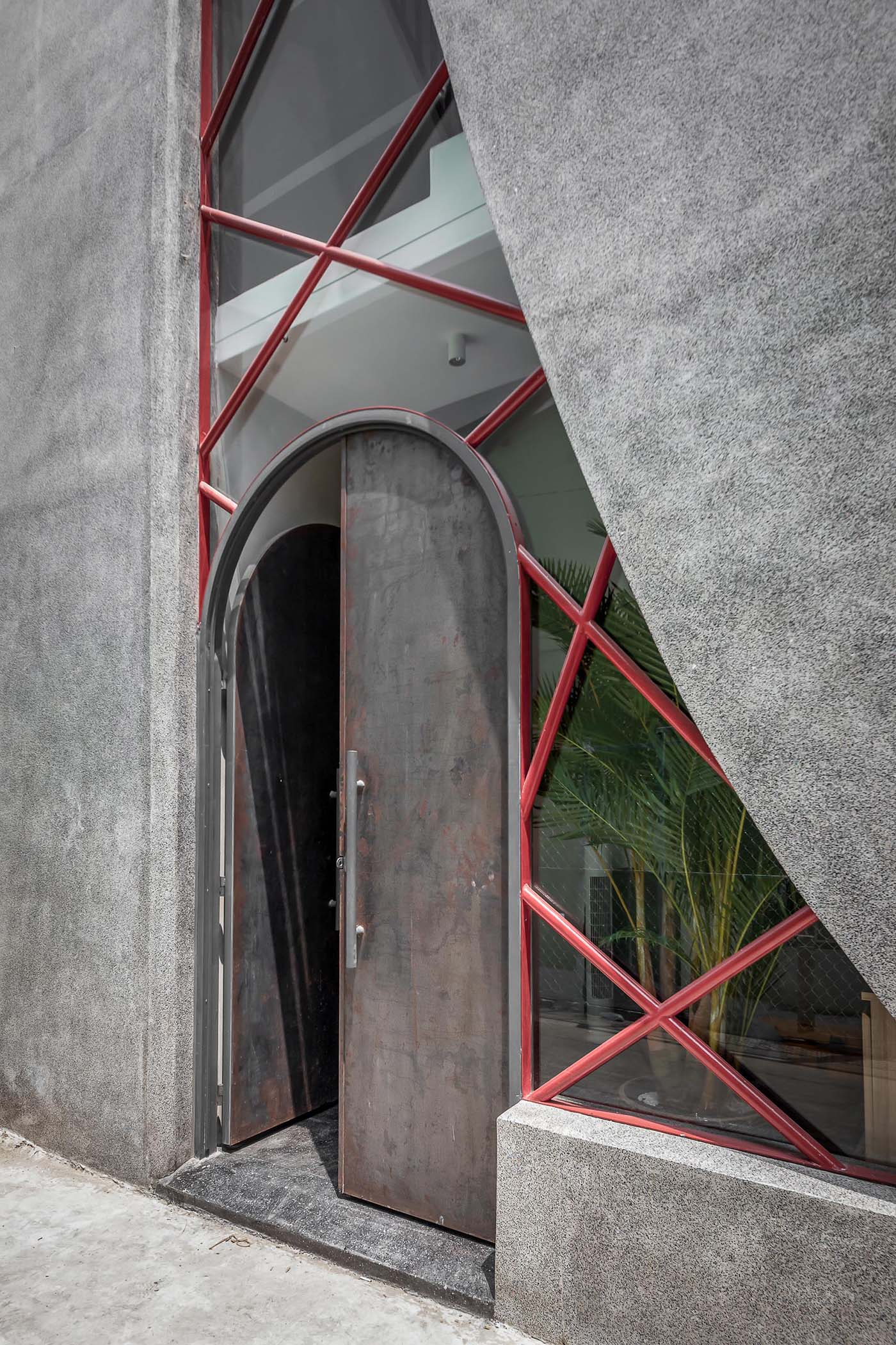 The large arched front door is made from steel, giving it an industrial look when paired with the concrete exterior.