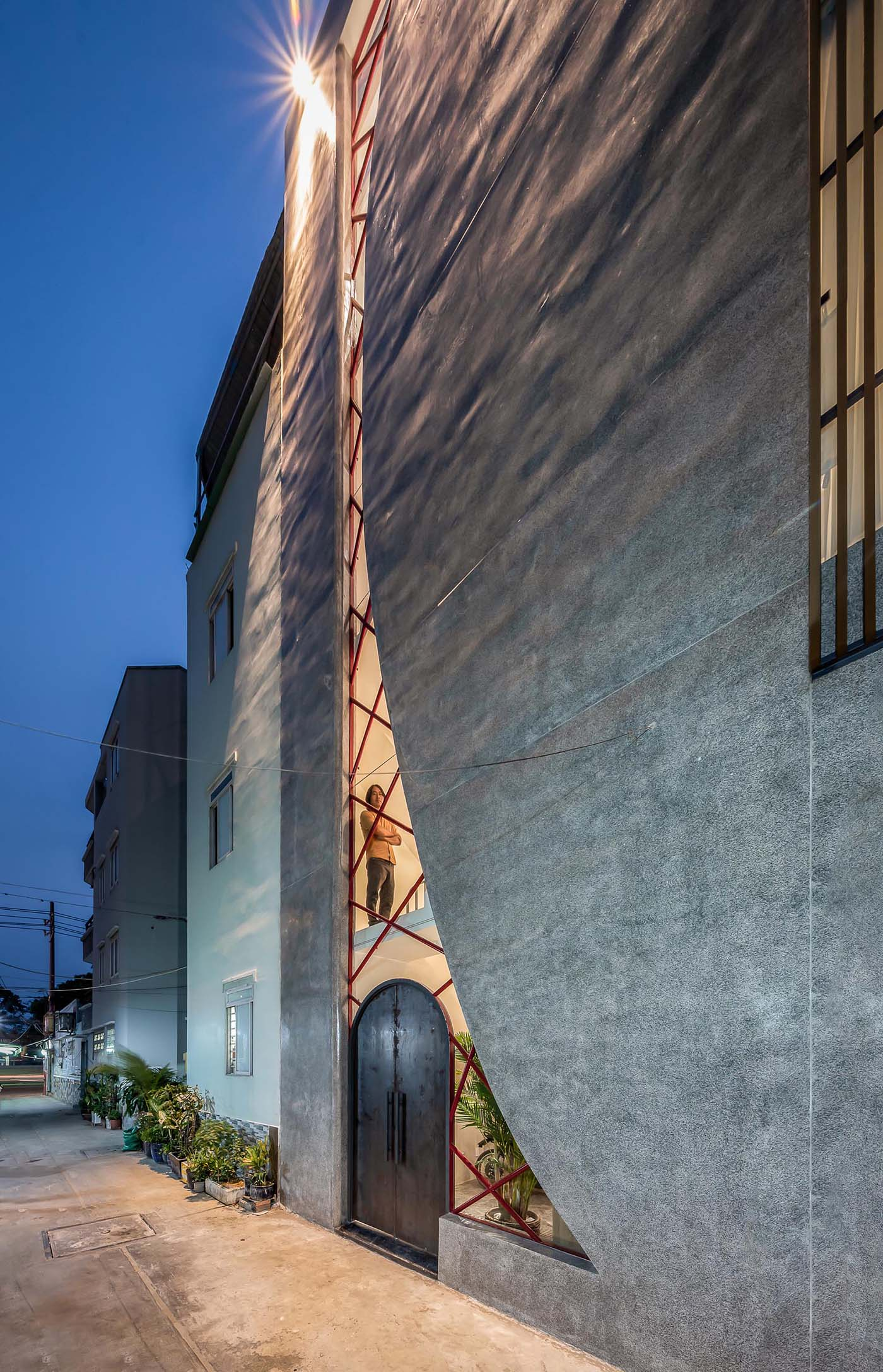 A modern concrete house with an irregular shaped window, also incorporates the steel arched front door.