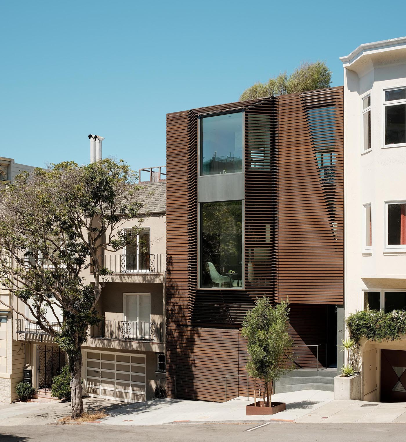A modern home with a wood exterior and bay windows.