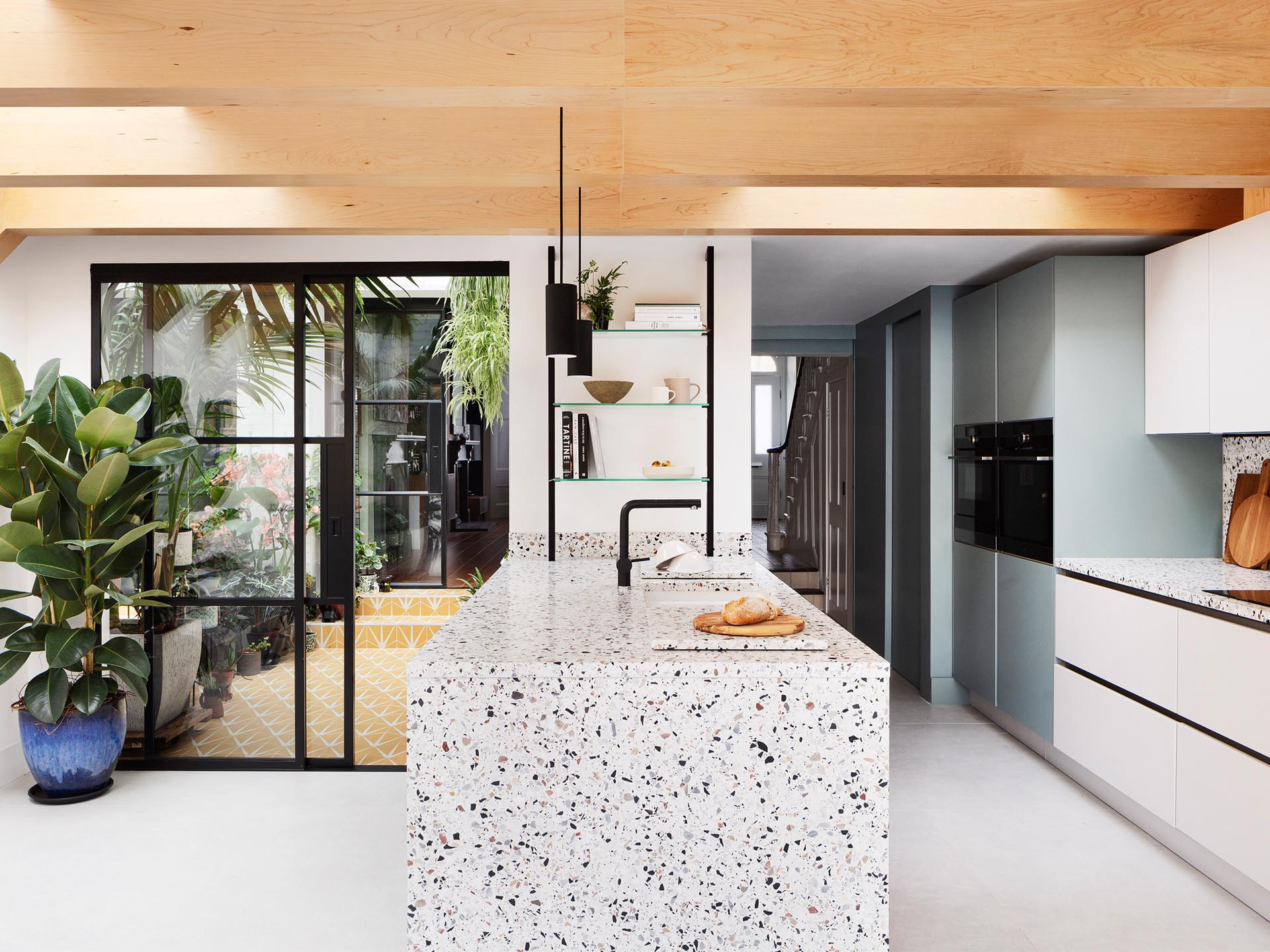 The warmth of the wood beams is mirrored in the neutral tones of the terrazzo that covers the kitchen island and countertops below, and in the muted green paintwork of cabinetry.