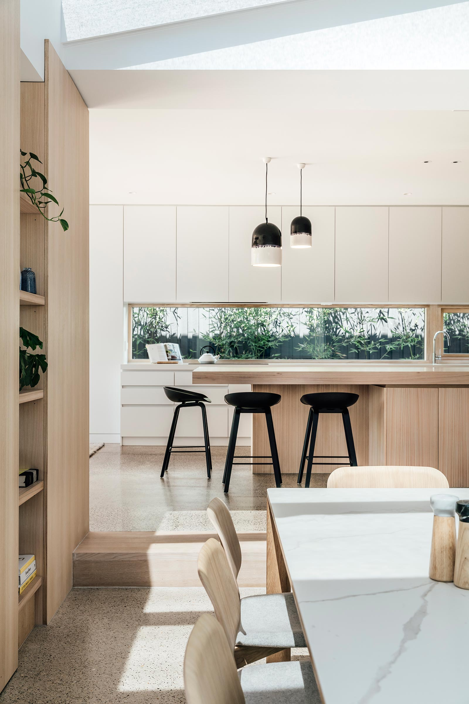 A modern kitchen with minimalist white and wood cabinets, and a window that acts as a backsplash.