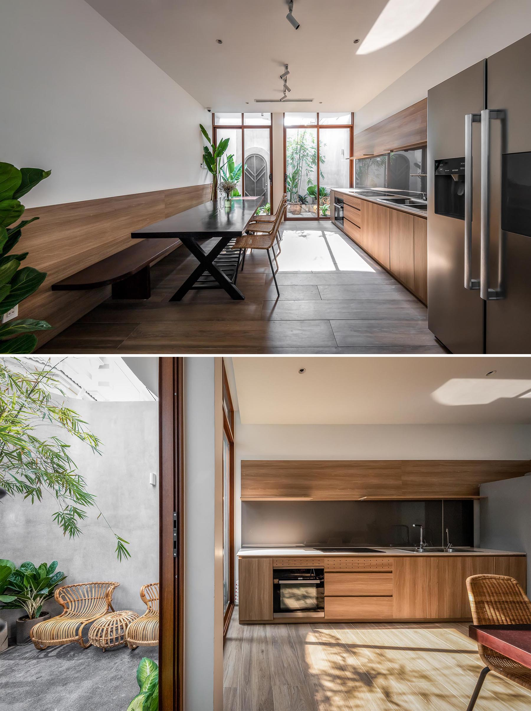 An open plan dining room and kitchen, where wood elements, like the dining bench and kitchen cabinets, complement the natural greenery of the indoor plants.