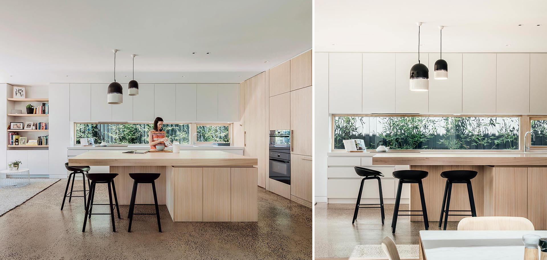A modern open plan kitchen with minimalist white and wood cabinets, and a window that acts as a backsplash.