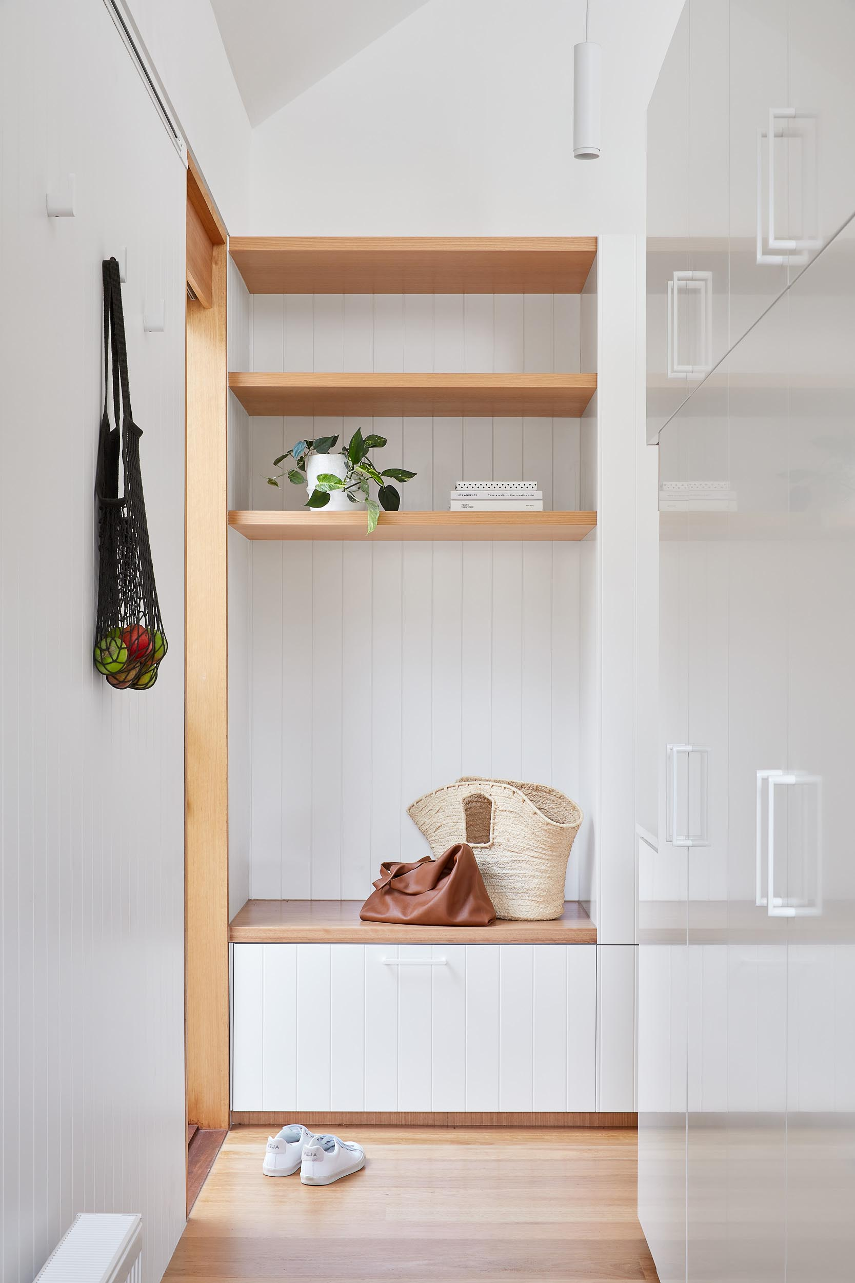 A laundry room behind the kitchen includes a wood bench and open shelving.