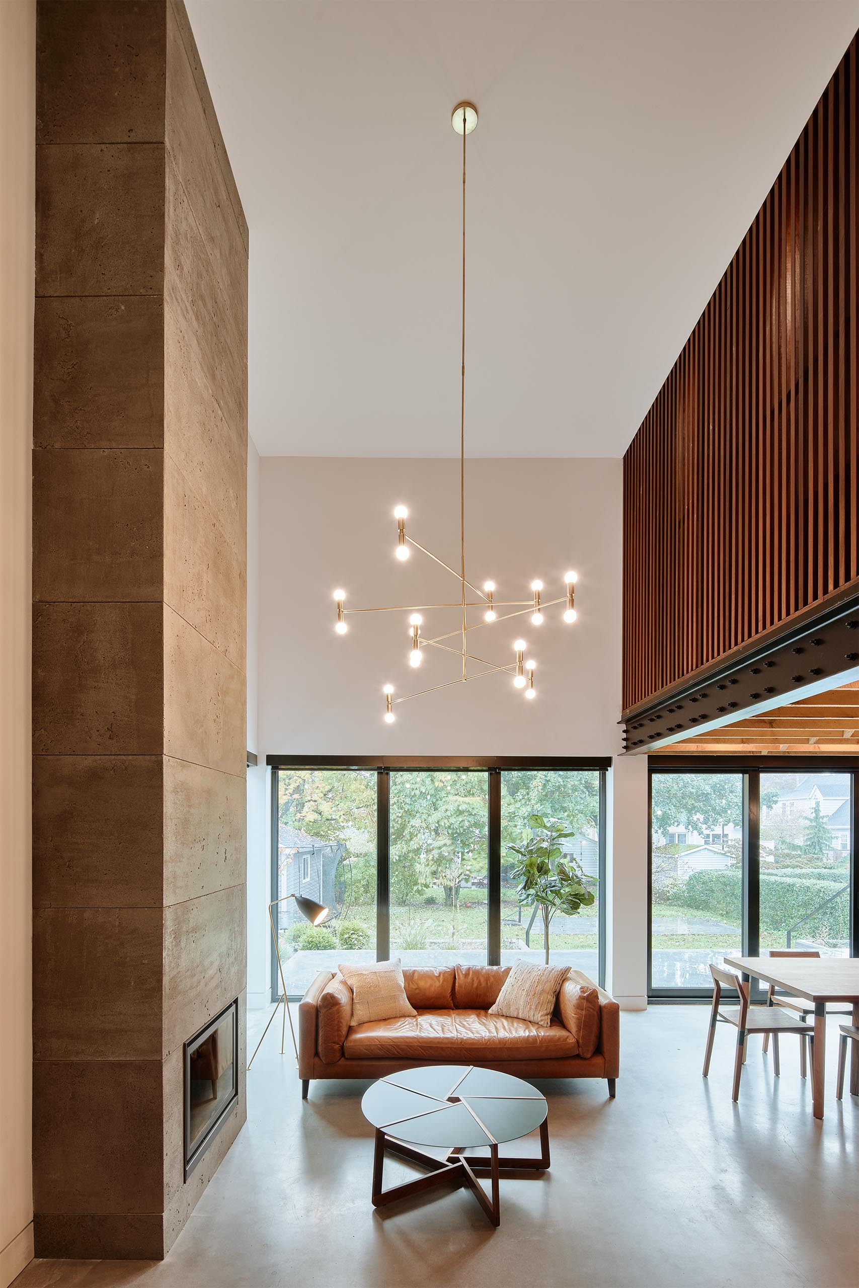 This modern living room has a double height ceiling, a fireplace, and a modern chandelier.